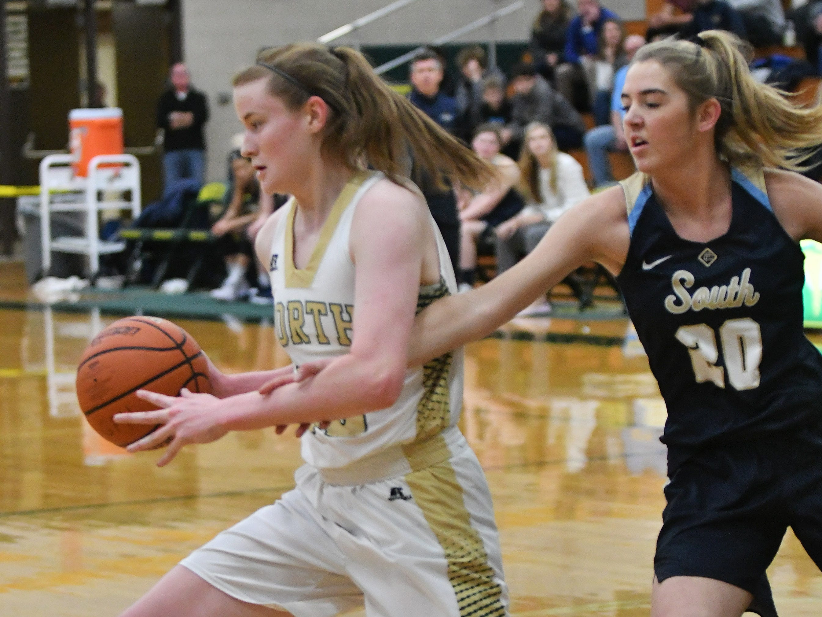 Grosse Pointe South's Cameron Lyndh reaches in on Grosse Pointe North's Julia Ayrault in the first quarter.