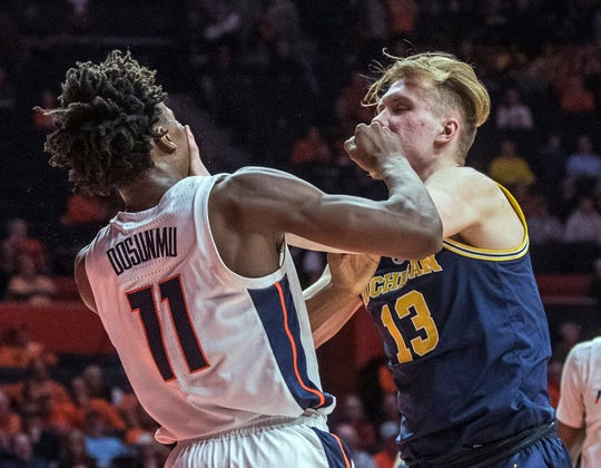 Illinois guard Ayo Dosunmu and Michigan forward Ignas Brazdeikis tangle after a foul during the second half.