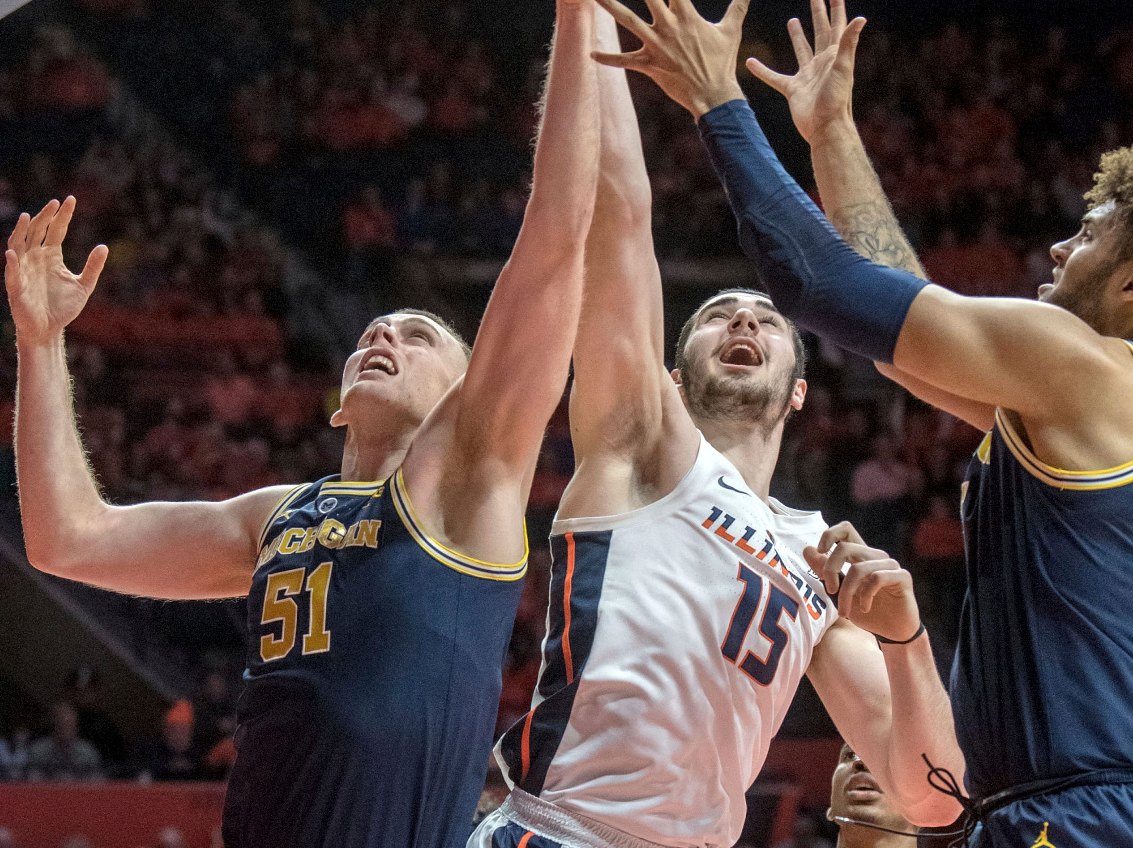 Michigan forward Austin Davis (51) and Michigan forward Isaiah Livers (4) go up for a rebound with Illinois forward Giorgi Bezhanishvili during the first half.