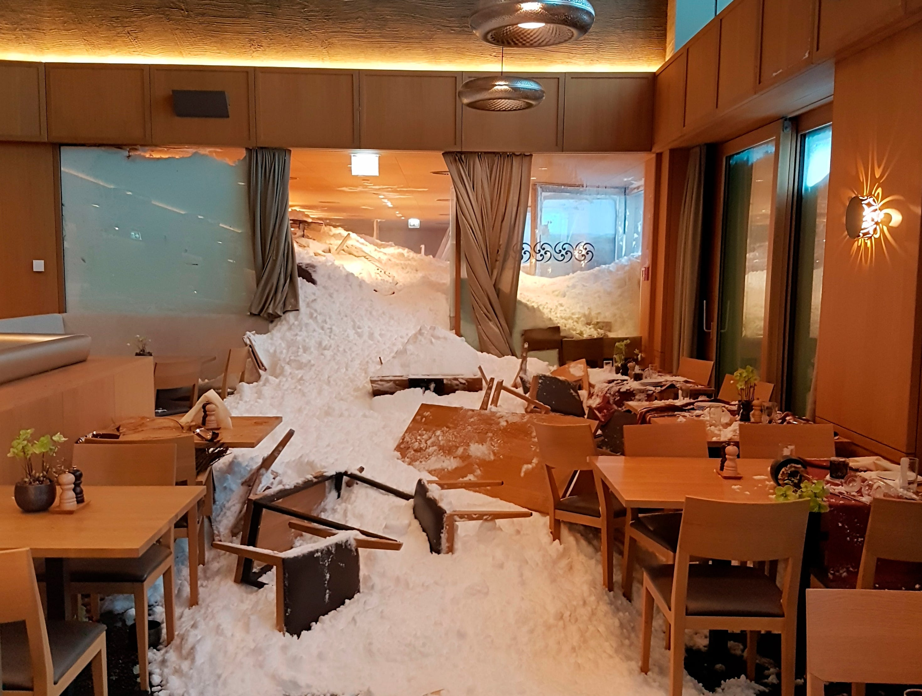 Snow enters the inside of the Hotel Saentis on the Schwaegalp, Switzerland, Thursday Jan. 10, 2019, after an avalanche. Police said three people were slightly hurt when the avalanche hit the hotel at Schwaegalp on Thursday afternoon.