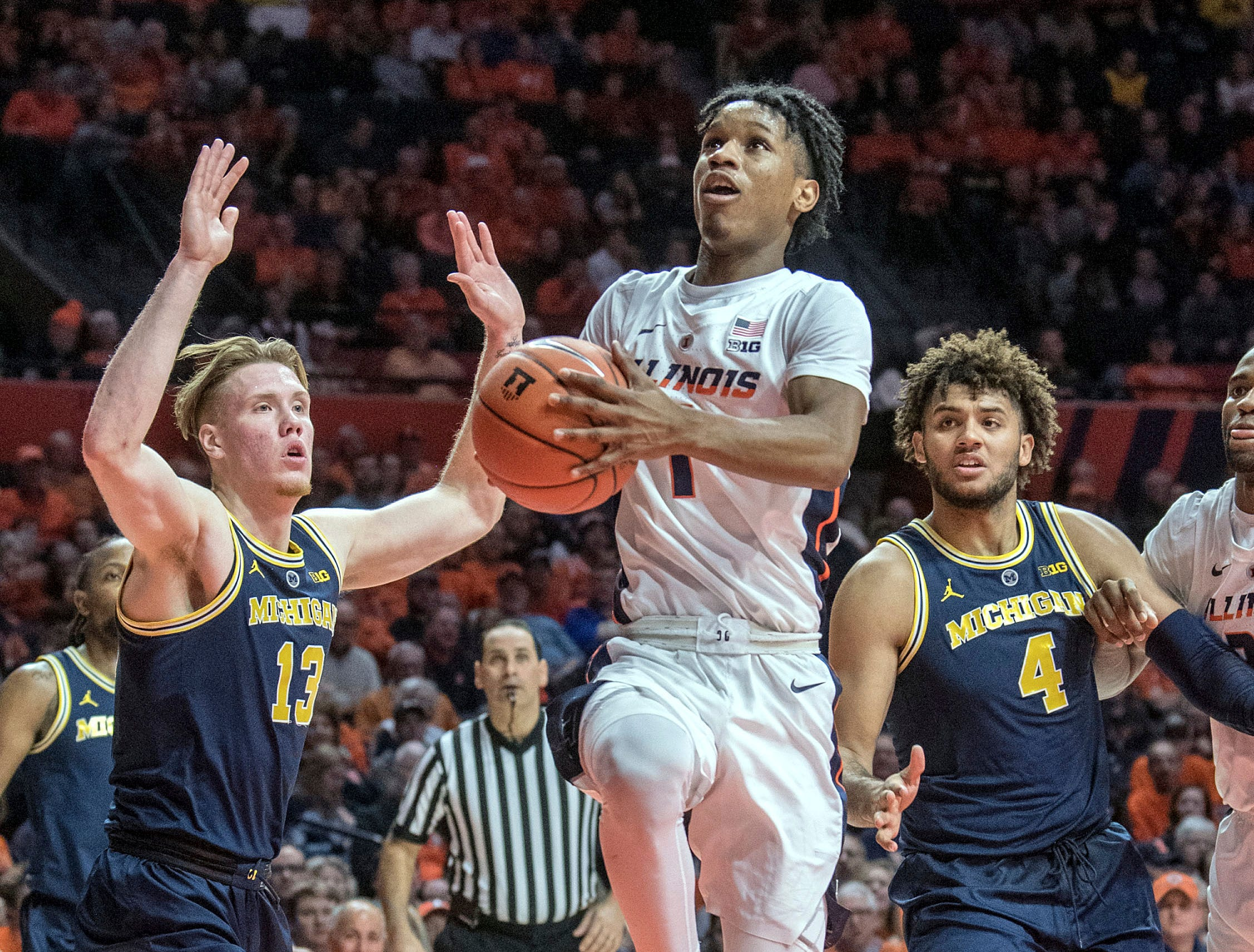 Illinois guard Trent Frazier (1) drives to the basket between Michigan forwards Ignas Brazdeikis (13) and Isaiah Livers (4) during the first half.