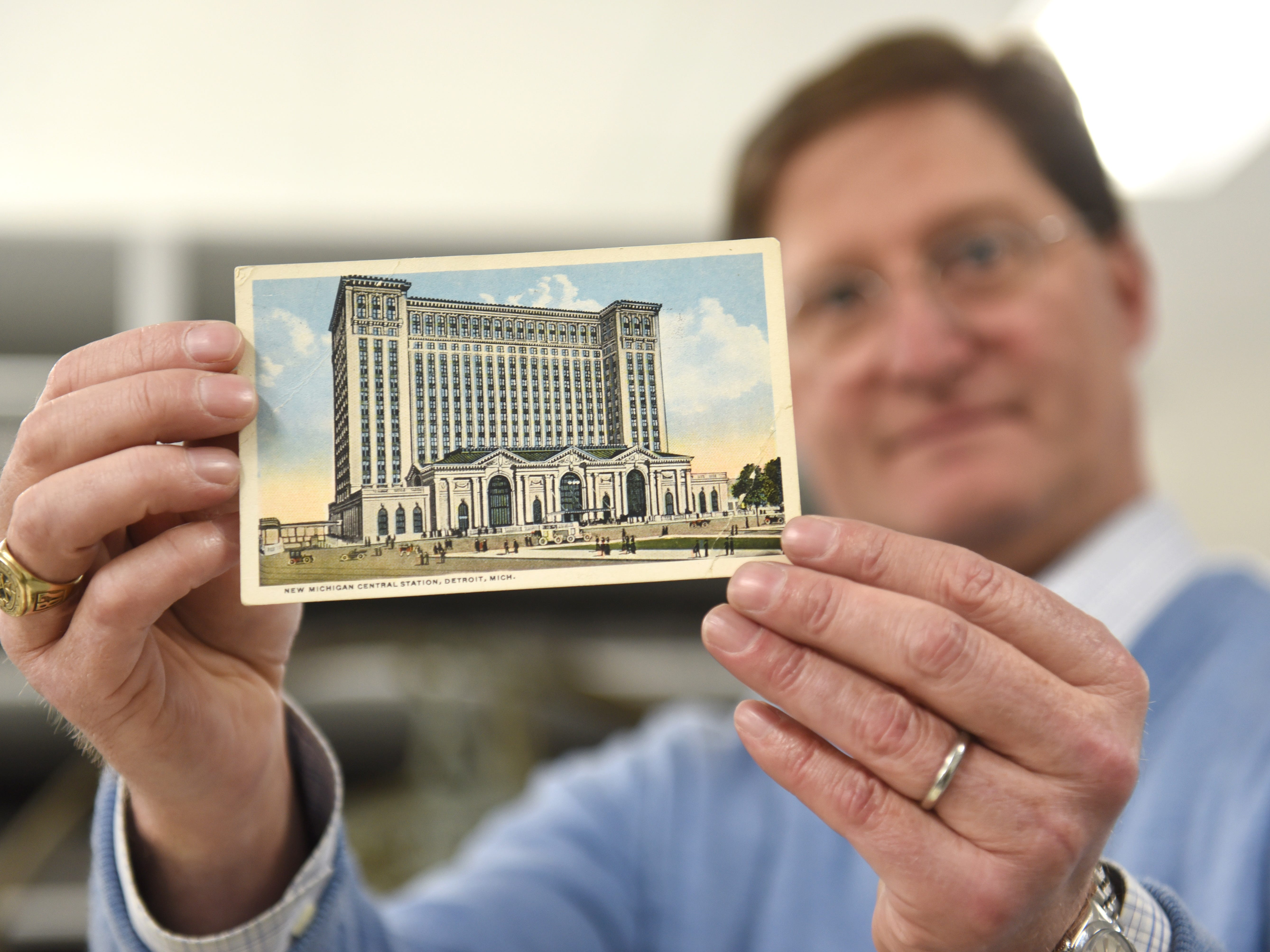 Ted Ryan, heritage brand manager, Ford Archives, holds a postcard from 1916 in Dearborn on Friday, Jan. 11, 2019, which will be part of a display at the Michigan Central Train Station. Ryan displayed many items which will be displayed at the Michigan Central Station's Winter Festival on Jan. 18-27.