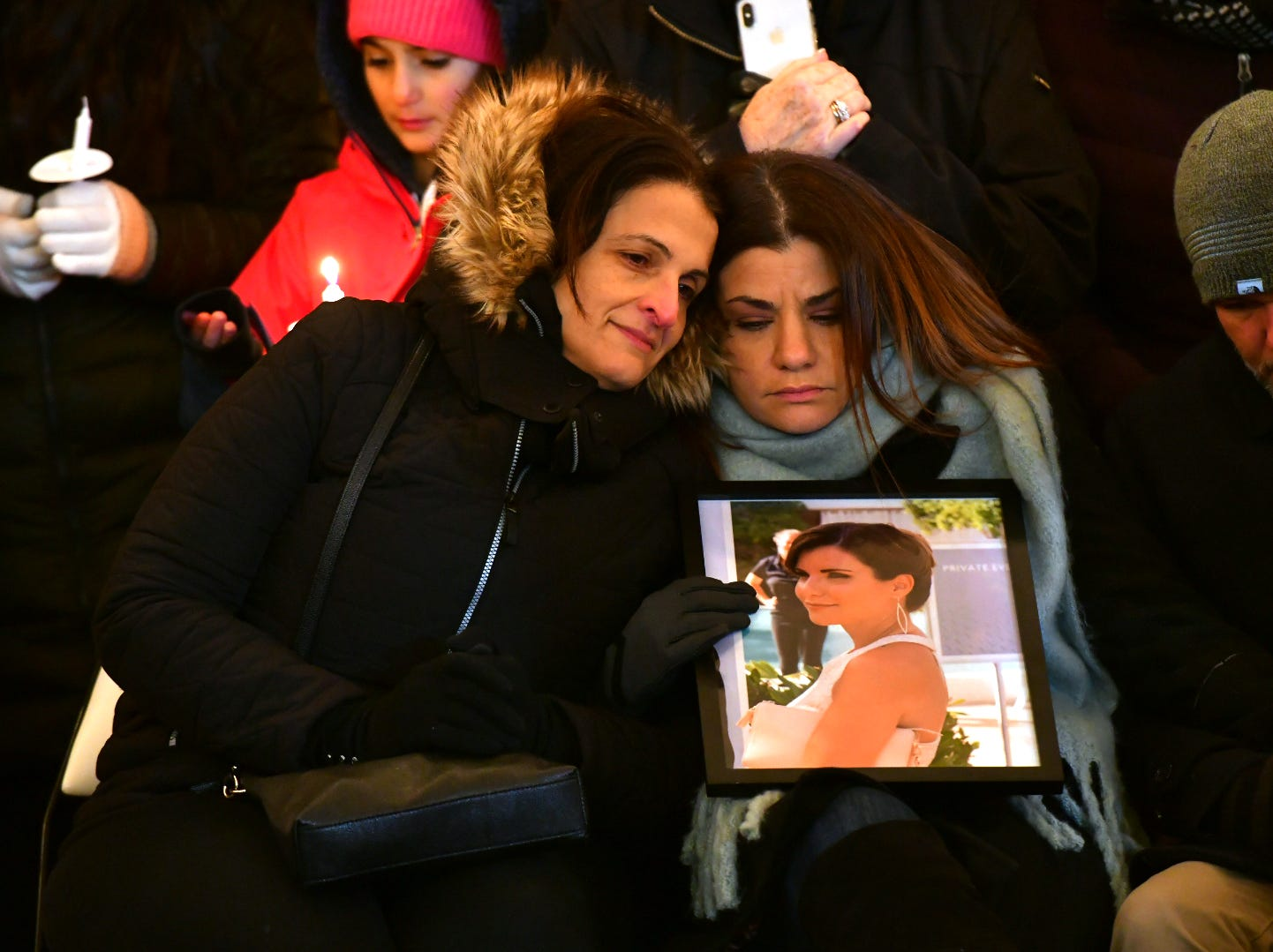 Rana Abbas Taylor (right) holds a picture of her sister Rima Abbas, who died along with her husband and three children in a tragic car accident, during a candlelight vigil in memory of the Northville family.