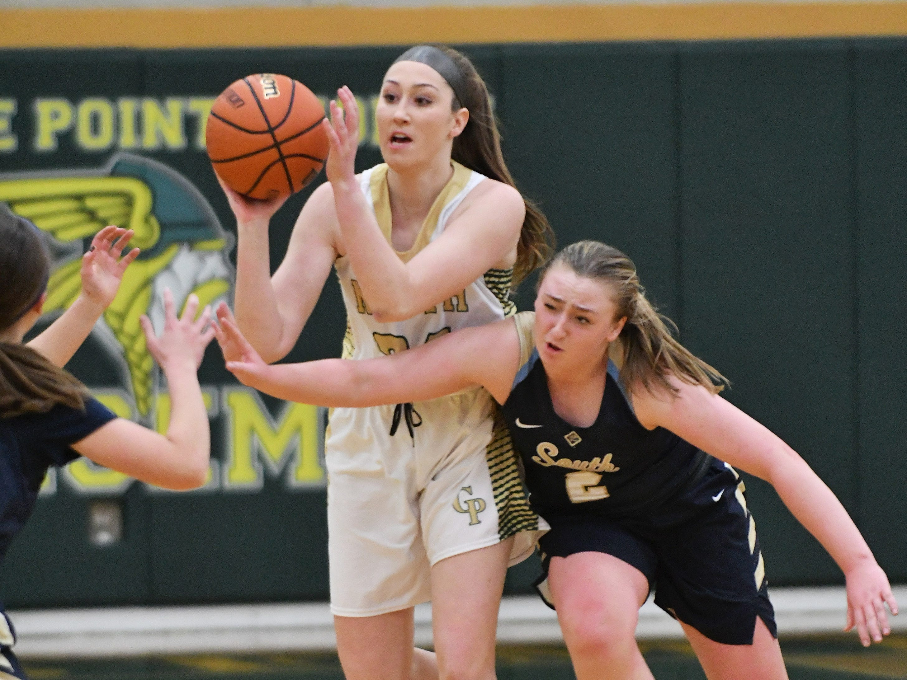 Grosse Pointe South's Alexa Downey (2) fouls Grosse Pointe North's Regan Sliwinski in the second quarter.