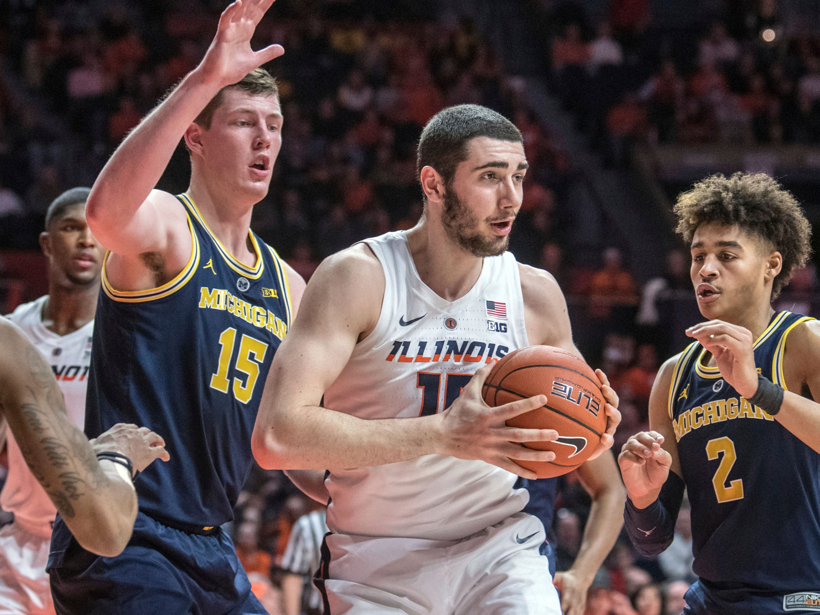 Illinois forward Giorgi Bezhanishvili (15) pulls down a rebound between Michigan center Jon Teske (15) and guard Jordan Poole (2) during the first half.