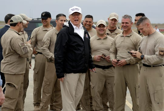President Donald Trump turns as he talks to U.S. Customs and Border Protection officers at McAllen International Airport as he prepares to leave after a visit to the southern border, Thursday, Jan. 10, 2019, in McAllen, Texas.