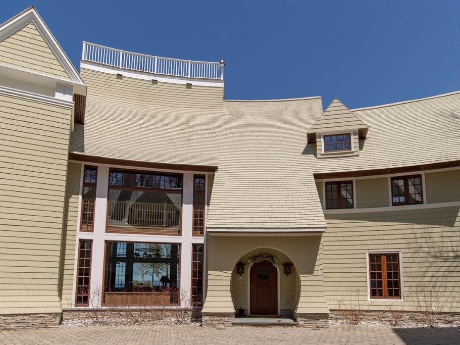 The home's exterior features cedar shakes roofing, cedar siding and custom stone.