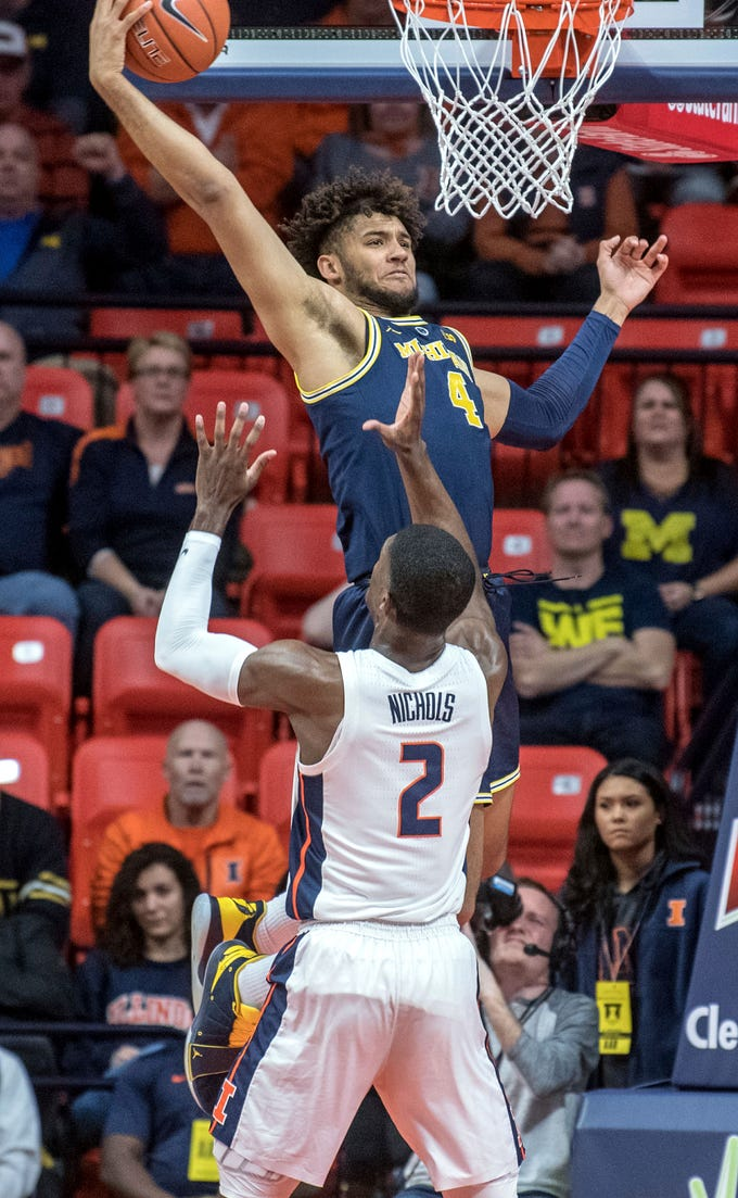 Michigan forward Isaiah Livers (4) goes up for a rebound over Illinois forward Kipper Nichols (2) during the first half of an NCAA college basketball game in Champaign, Ill., Wednesday, Jan. 10, 2019.  Michigan defeated Illinois 79-69.