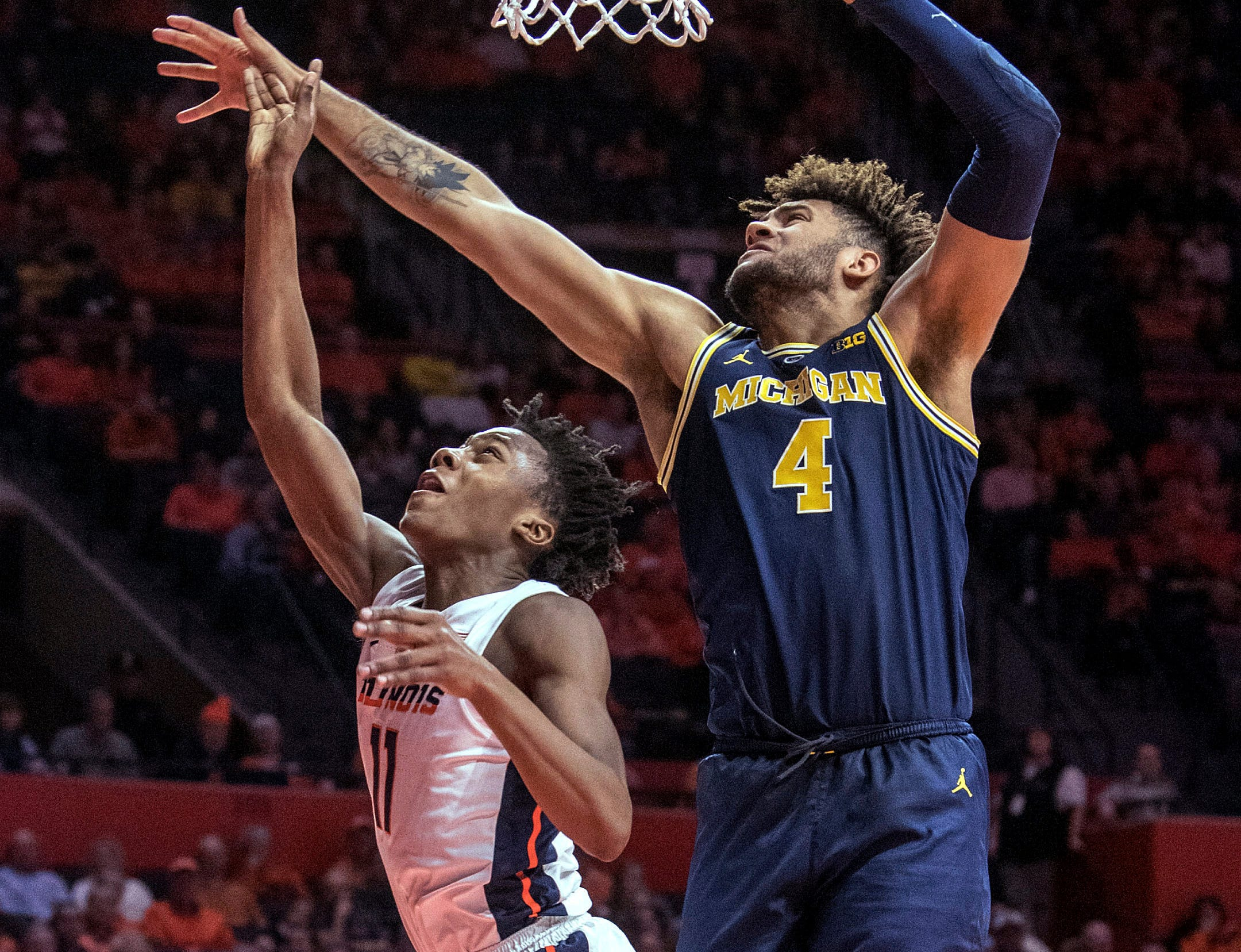 Illinois guard Ayo Dosunmu (11) shoots next to Michigan forward Isaiah Livers (4) during the first half.