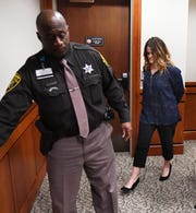 Teacher Kathryn Houghtaling is led from the court into lockup after her arraignment  on charges of sexual misconduct with Rochester High School students at 52-3 District Court in Rochester Hills, Friday.