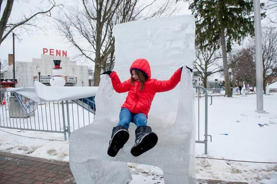 Five-year-old Ryen Mahoney (cq on Ryen), of Plymouth hangs out on a throne carved from ice at the Plymouth Ice Festival, in downtown Plymouth, January 10, 2016.  (David Guralnick / The Detroit News)