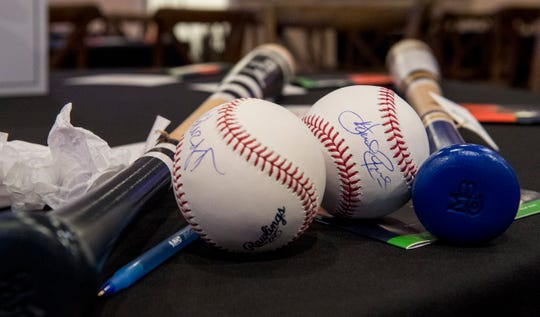 The one-of-a-kind baseball bats and balls signed by Comedian Joe Piscopo and television baseball analyst Harold Reynolds rest on a table before being auctioned off during the Mattingly Charities Find a Way event in Evansville, Ind. Thursday, Jan. 10, 2019.