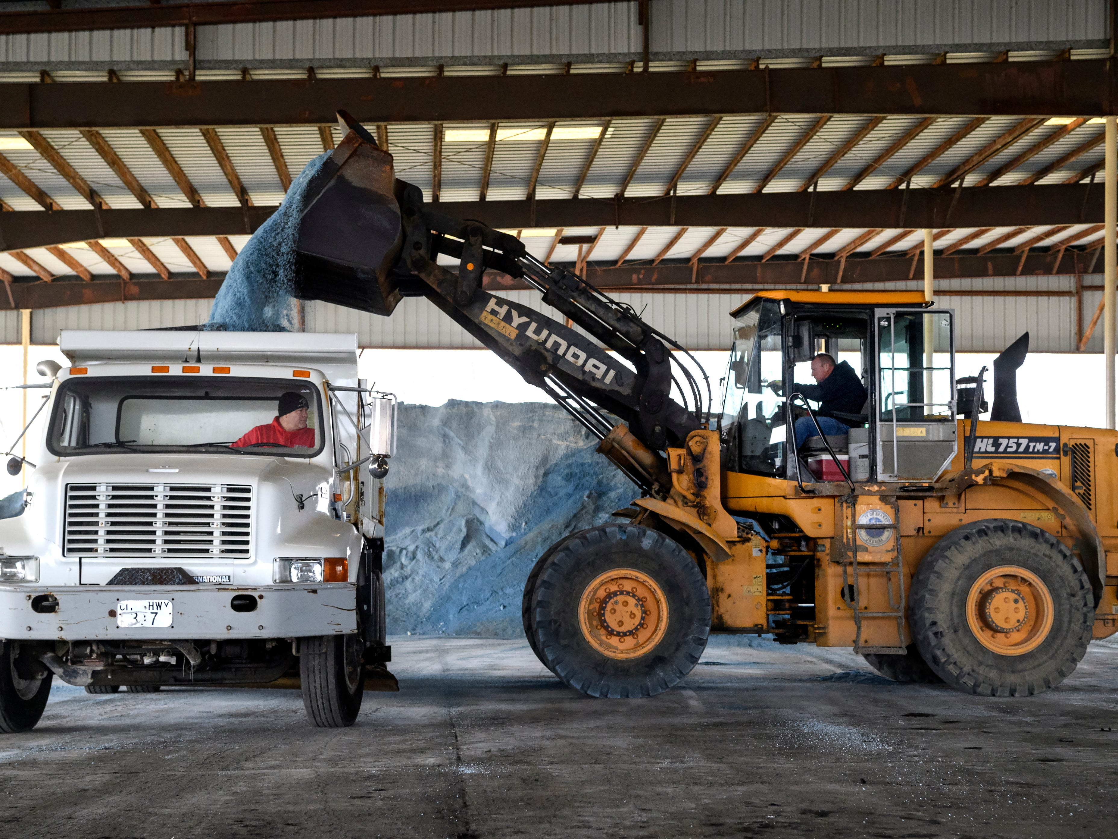 Brad Haller, right, an operator for the City of Evansville's Street Maintenance department, dumps salt into his co-worker Jody Goodwin's truck at the salt barn located in the East Waste Water Treatment plant in Evansville, Ind., Friday, Jan. 11, 2019. The city scheduled for twelve trucks to start treating roads at 6 p.m. Friday, when a Winter Storm warning issued by the National Weather Service went into effect.