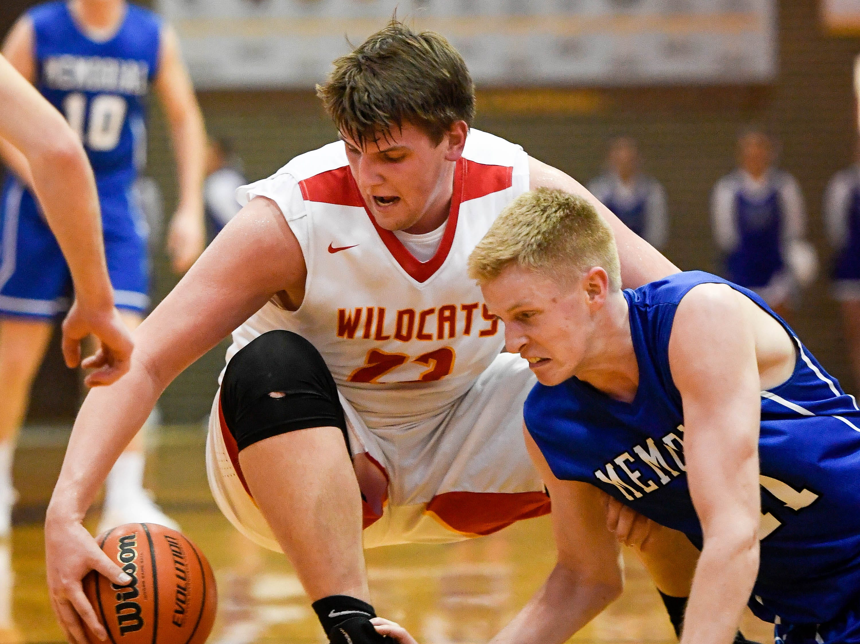 Mater Dei's Logan Carter (23) and Memorial's Sam DeVault (41) scramble for a loose ball as the Memorial Tigers play the Mater Dei Wildcats in the Southern Indiana Athletic Conference semi-finals at Central High Thursday, January 10, 2019.