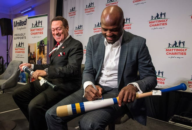 Comedian Joe Piscopo, left, and television baseball analyst Harold Reynolds sign one-of-a-kind baseball bats to be auctioned off before the Mattingly Charities Find a Way event in Evansville, Ind. Thursday, Jan. 10, 2019.