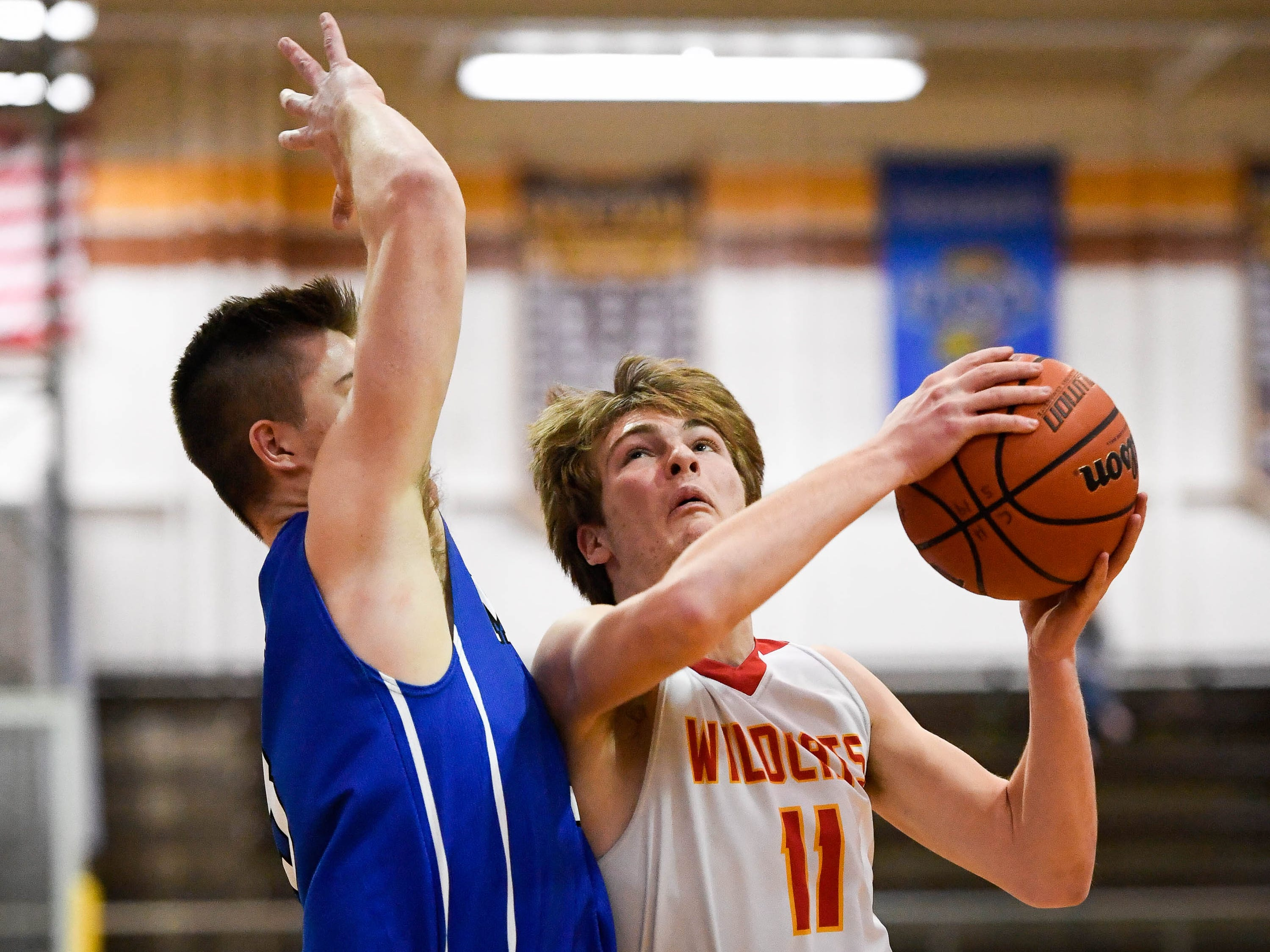 Mater Dei's Dawson Caswell (11) looks to shoot over Memorial's Branson Combs (3) as the Memorial Tigers play the Mater Dei Wildcats in the Southern Indiana Athletic Conference semi-finals at Central High Thursday, January 10, 2019.