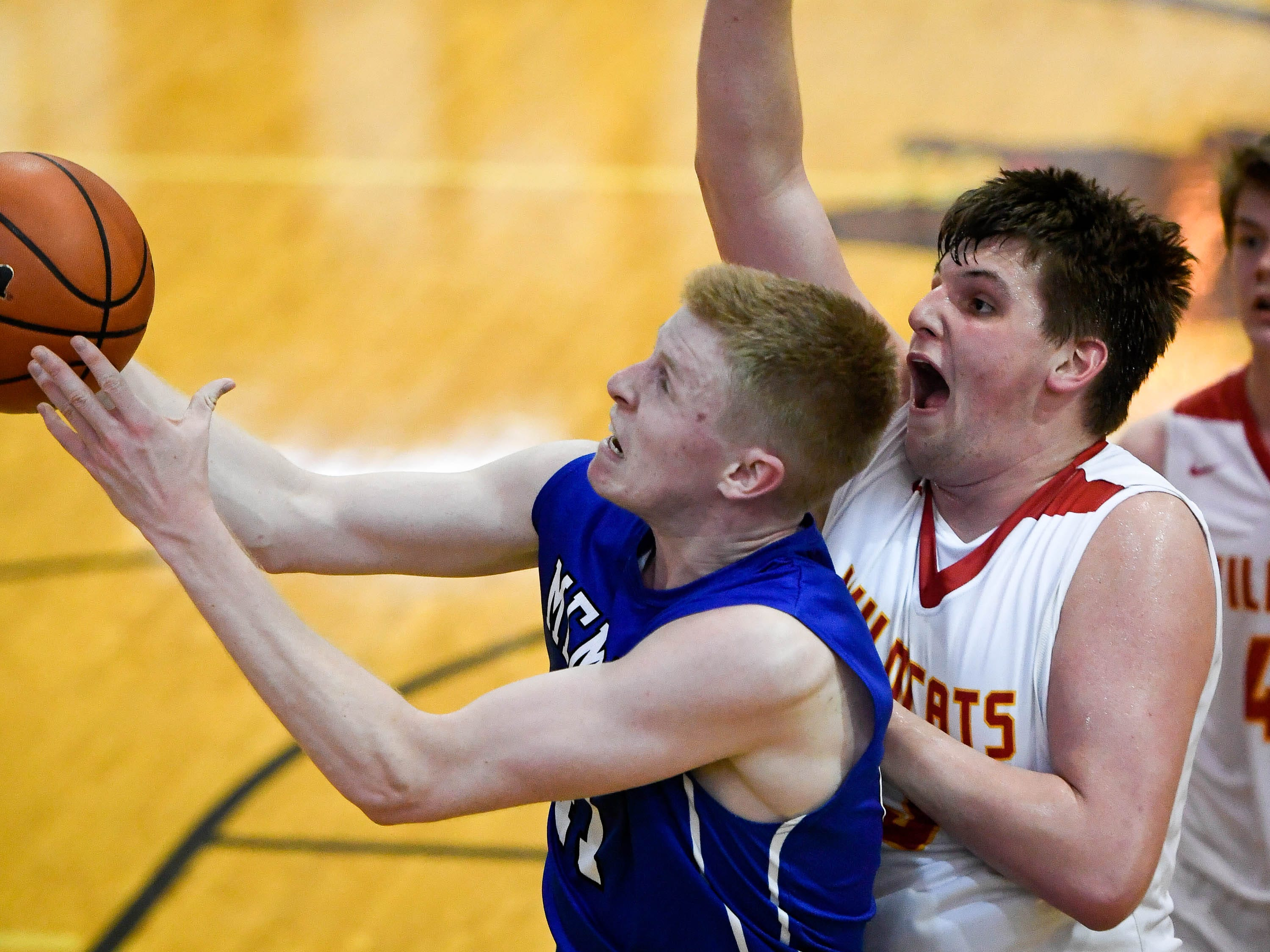 Memorial's Sam DeVault (41) looks to shoot under defensive pressure from Mater Dei's Logan Carter (23) as the Memorial Tigers play the Mater Dei Wildcats in the Southern Indiana Athletic Conference semi-finals at Central High Thursday, January 10, 2019.