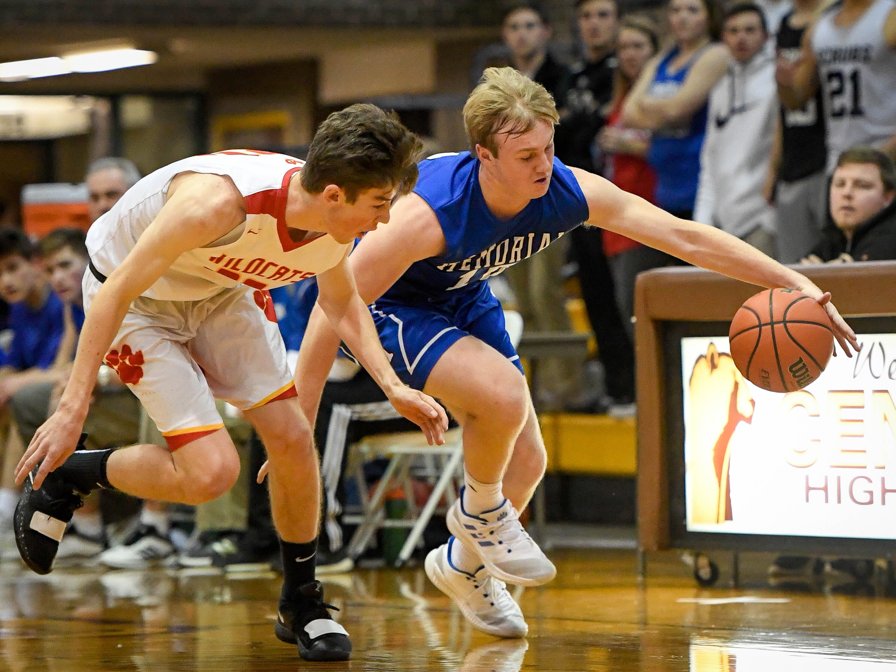 Mater Dei's Zach Schoenstein (30) and Memorial's Michael Lindauer (10) chase down a loose ball as the Memorial Tigers play the Mater Dei Wildcats in the Southern Indiana Athletic Conference semi-finals at Central High Thursday, January 10, 2019.