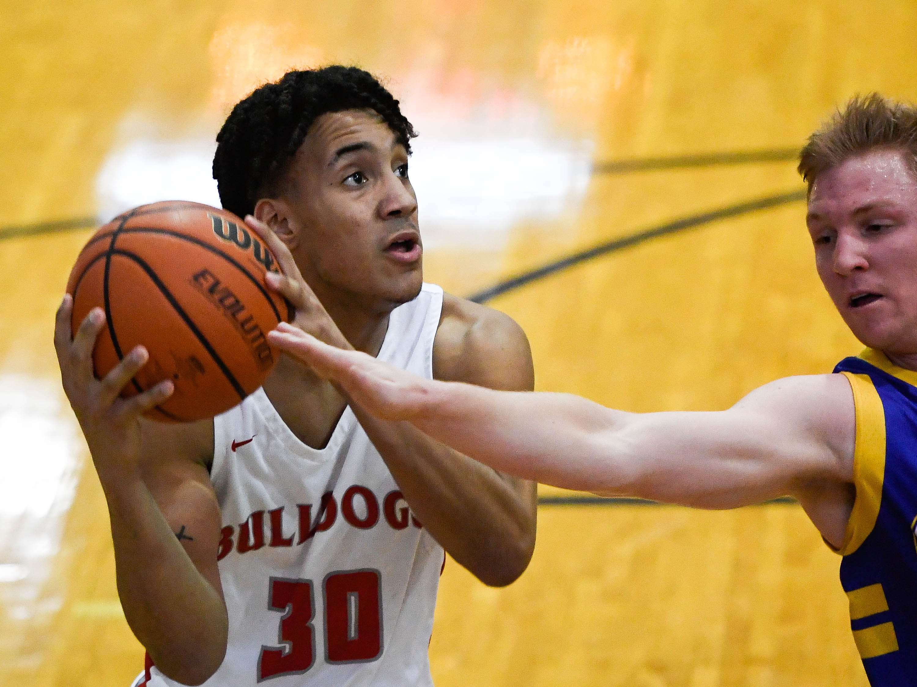 Bosse's Donovan Mcneal (30) looks to shoot under defensive pressure from Castle's Brycen Moore (30) as the Castle Knights play the Bosse Bulldogs in the Southern Indiana Athletic Conference semi-finals at Central High Thursday, January 10, 2019.