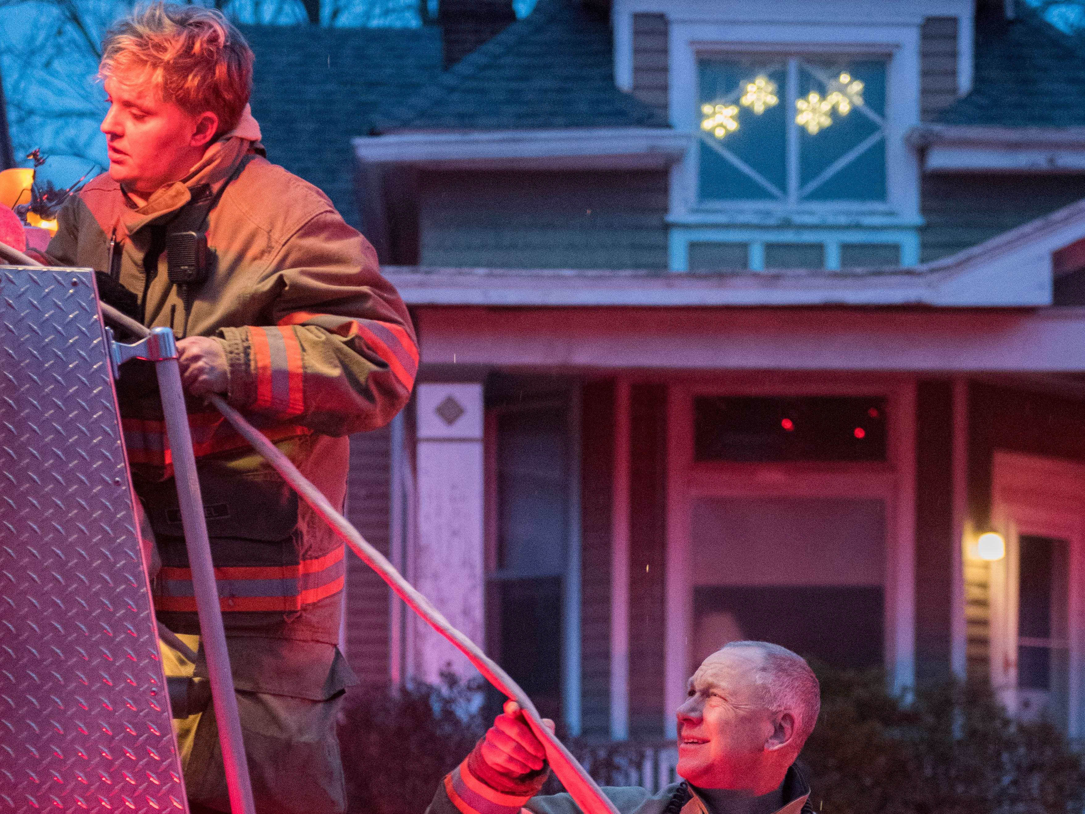 Evansville Fire Department's Jamie Phillips, left and Bryan Will load a hose back onto a firetruck while sleet falls Friday evening after responding to a house fire at 426 Adams Avenue in Evansville, Ind. Jan 11, 2019.