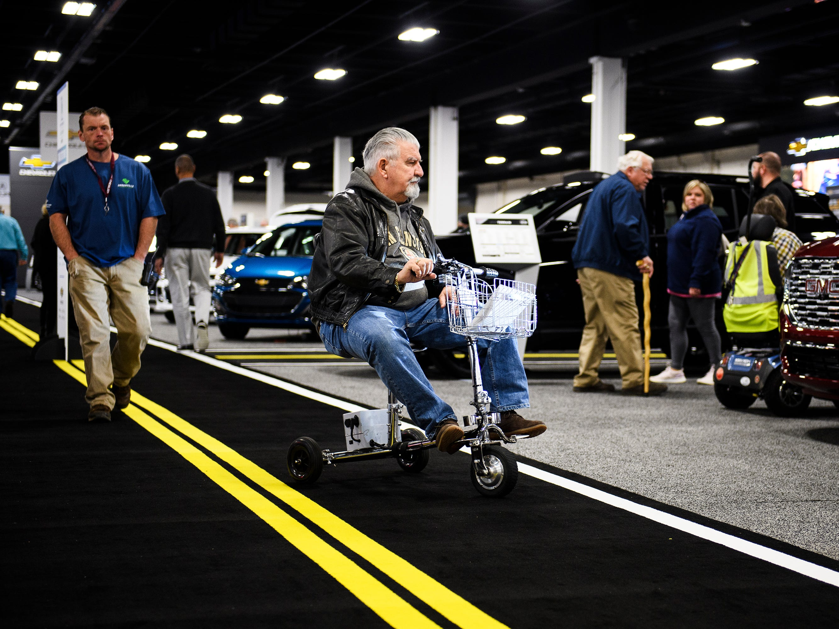 John Lentini rides his scooter down the walkway during the South Carolina International Auto Show Friday, Jan. 11, 2019 at the Greenville Convention Center.