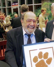 John Antonio, photographed April 14, 2007, holding the Tiger Paw logo he created in 1970. Antonio died in 2013 at 83.