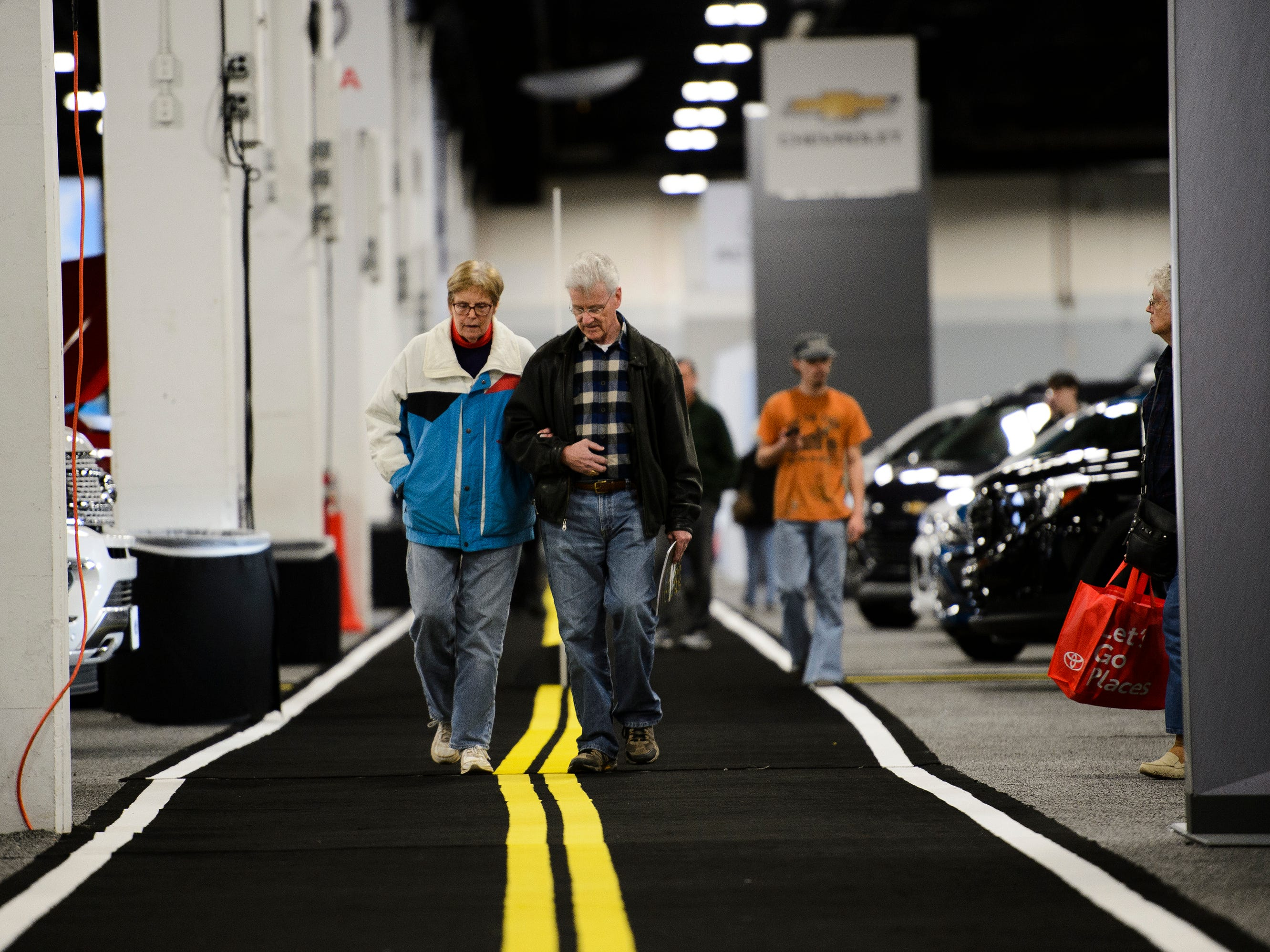 Chris and Barb Brooks walk down a road-themed walkway during the South Carolina International Auto Show Friday, Jan. 11, 2019 at the Greenville Convention Center.