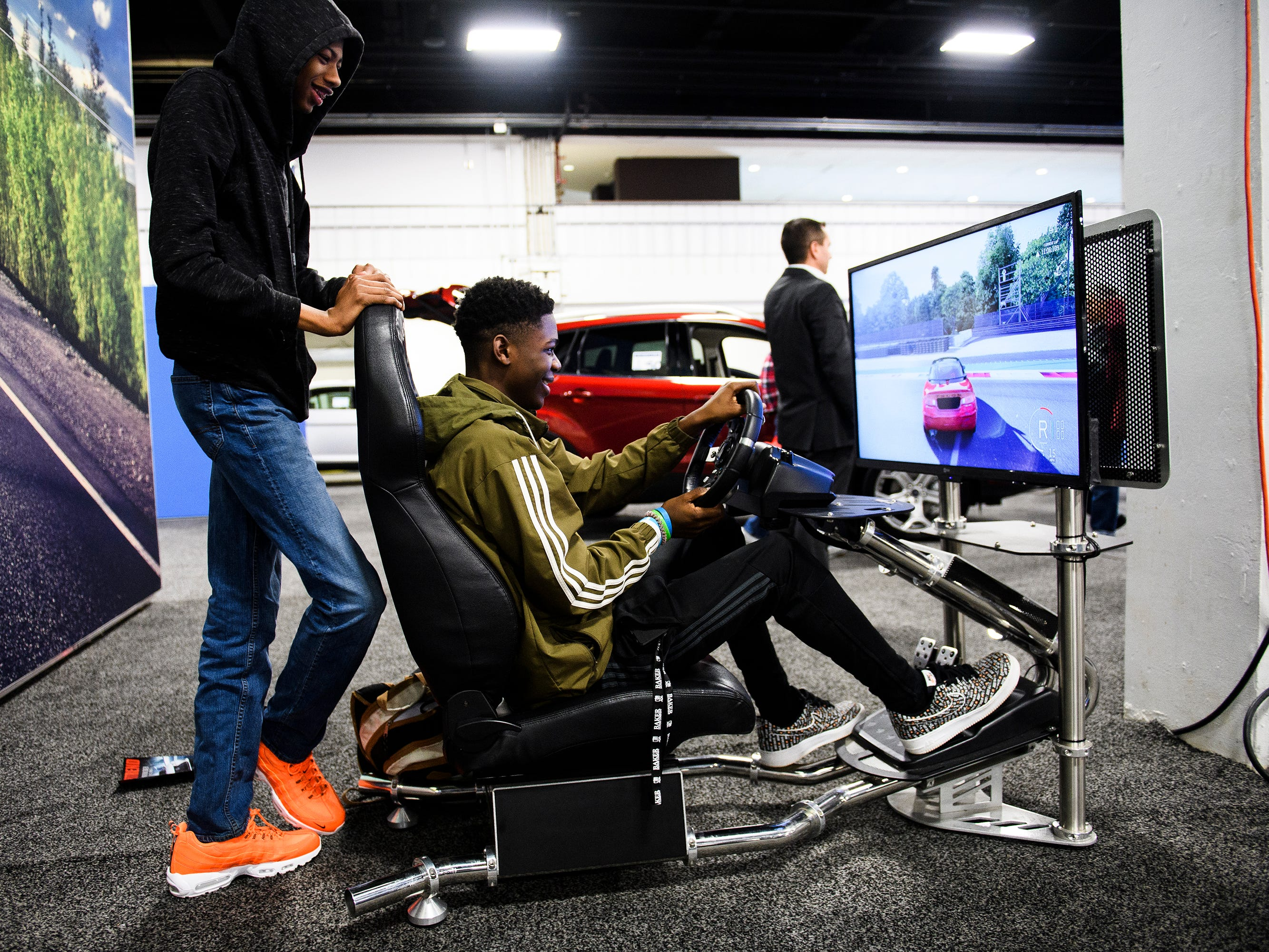 Jykee Whitfield plays a racing game as Tydriques Sullivan watches during the South Carolina International Auto Show Friday, Jan. 11, 2019 at the Greenville Convention Center.