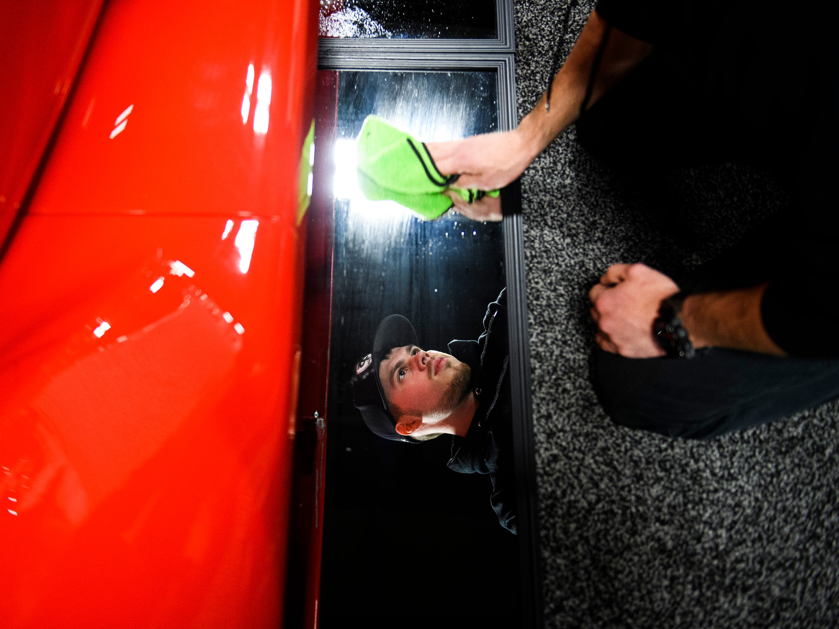 Brandon Woods cleans mirrors reflecting parts underneath a vehicle during the South Carolina International Auto Show Friday, Jan. 11, 2019 at the Greenville Convention Center.