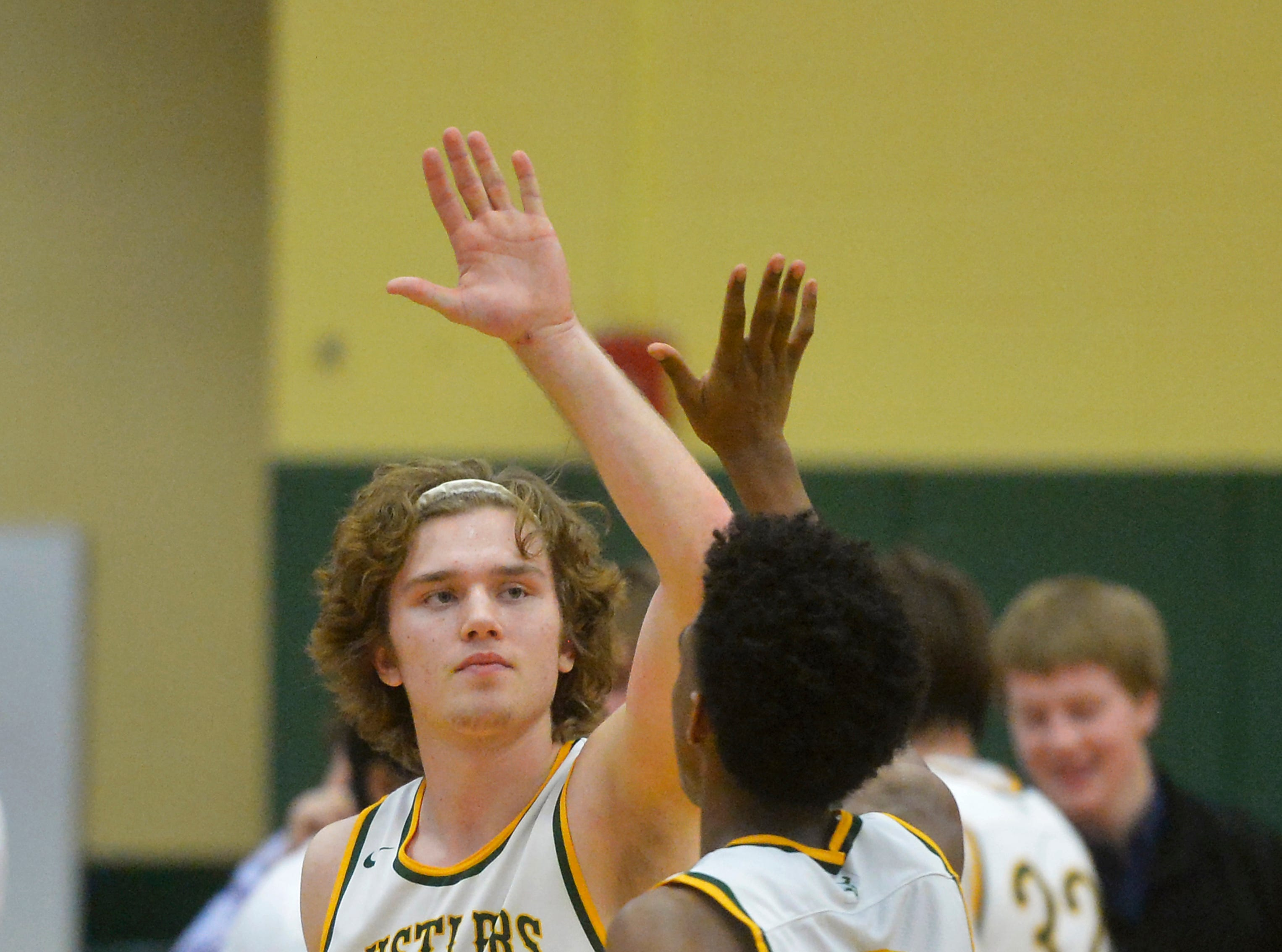 CMR's Keegan Barnes (22) and Caleb Curringtion slap a high five on the way to their bench during a timeout in Thursday's crosstown basketball game in the CMR Fieldhouse.