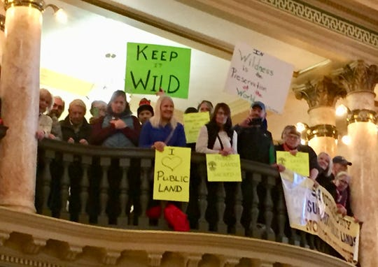 People look down from the third floor of the capitol rotunda Friday, clutching signs in support of public land.