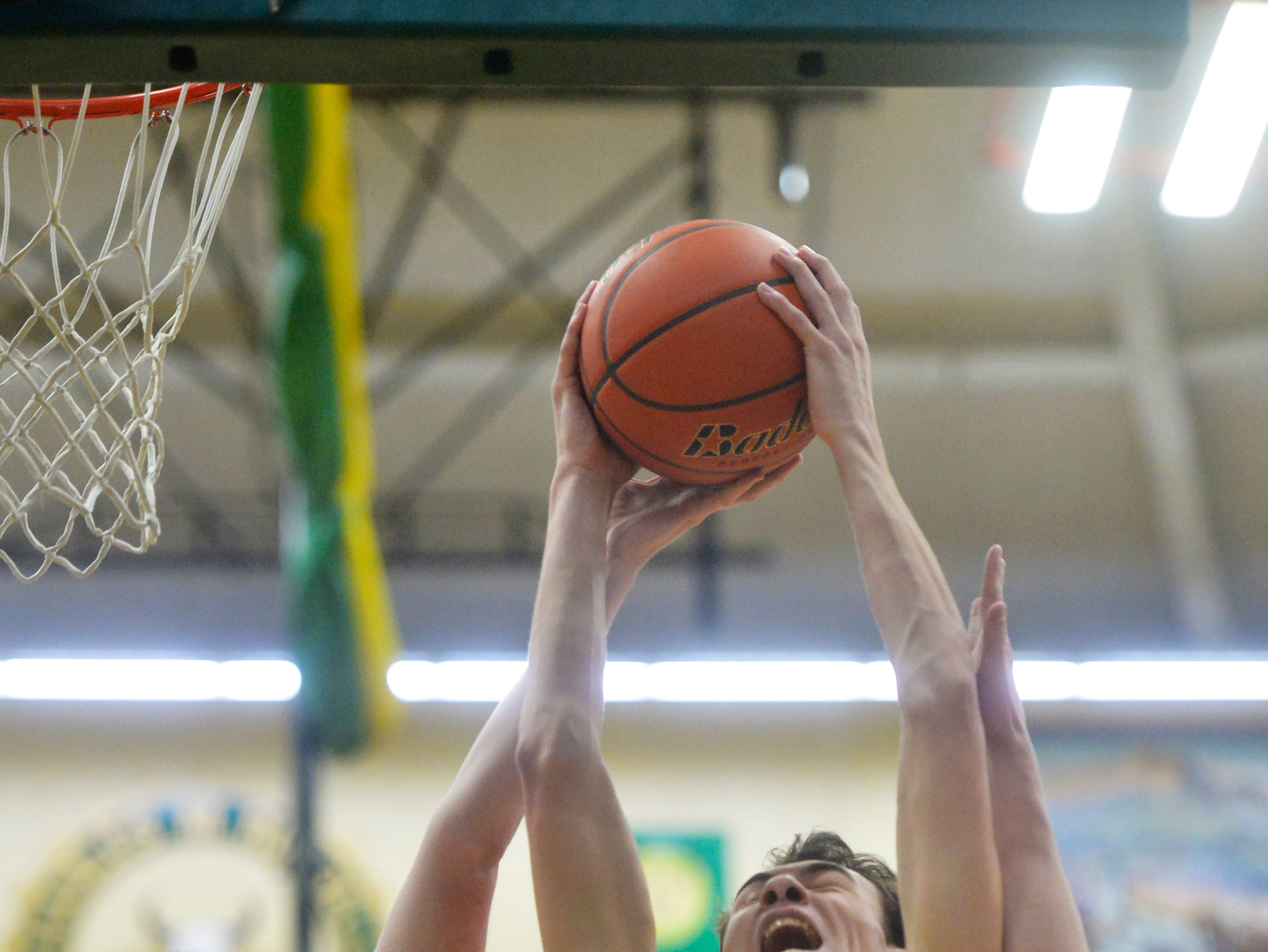 CMR's Russell Gagne grabs a rebound over Great Falls High's Drew Wyman during the crosstown basketball game, Thursday night, in the CMR Fieldhouse.