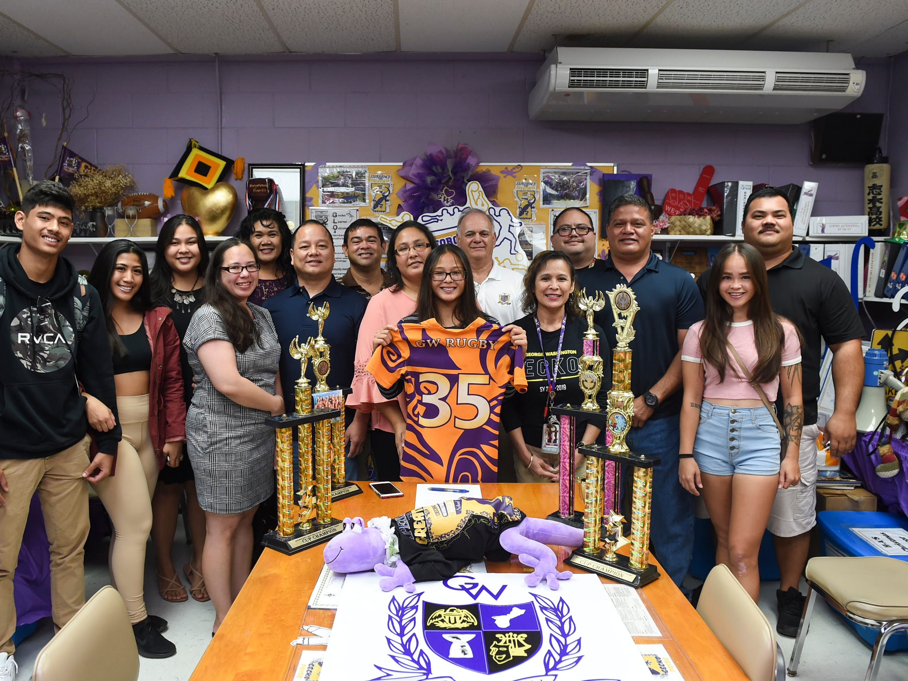 Family and George Washington High School staff members gather for the college signing of their girls' rugby star athlete, Jalana Garcia, 18, at the GWHS main office, Jan. 11, 2019. Garcia, a four-time All-Island athlete and rugby champion, has signed a letter of intent to play rugby for Mount St. Mary's University in Emmitsburg, Maryland.
