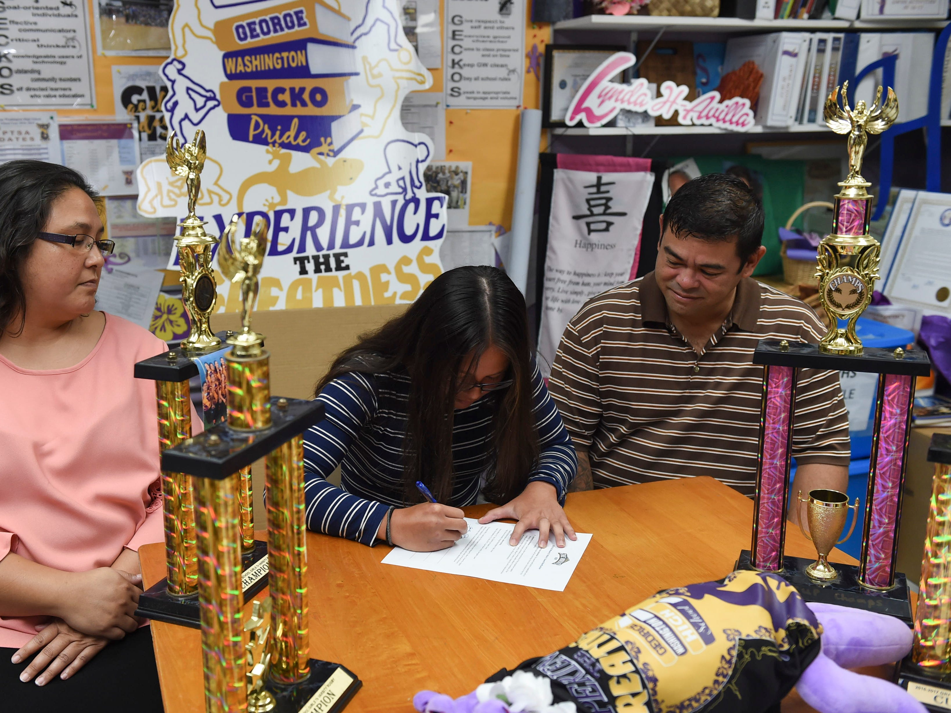 Jalana Garcia, 18, a George Washington girls' rugby star and All-Island athlete, signs a letter of intent to play for Mount St. Mary's University, beside her parents Ava and Jeffrey Garcia at the GWHS main office, Jan. 11, 2019.