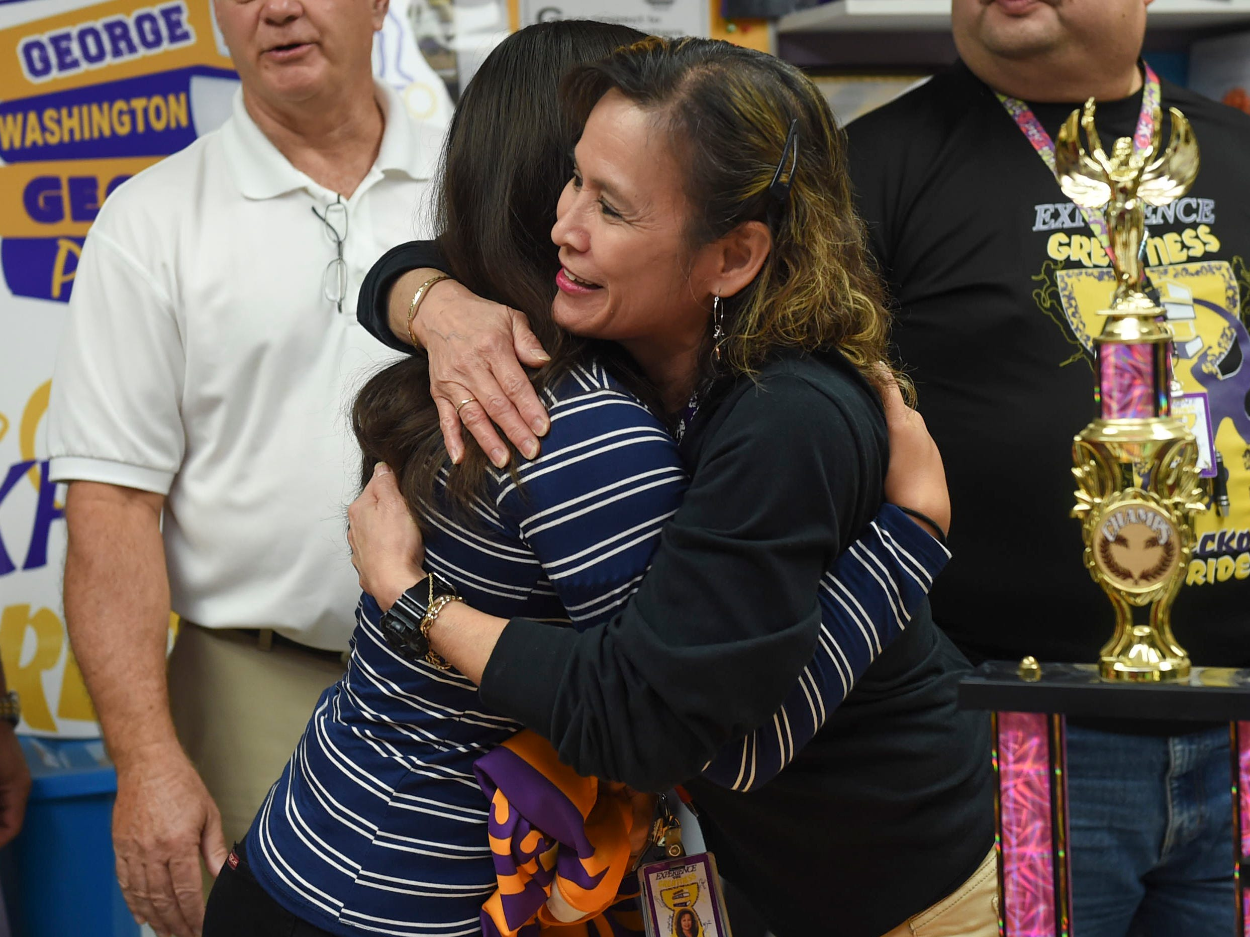 George Washington High School Principal Yolinda Hernandez-Avilla hugs Jalana Garcia, 18, following her signing with Mount St. Mary's University in Emmitsburg, Maryland, at the GWHS main office, Jan. 11, 2019.