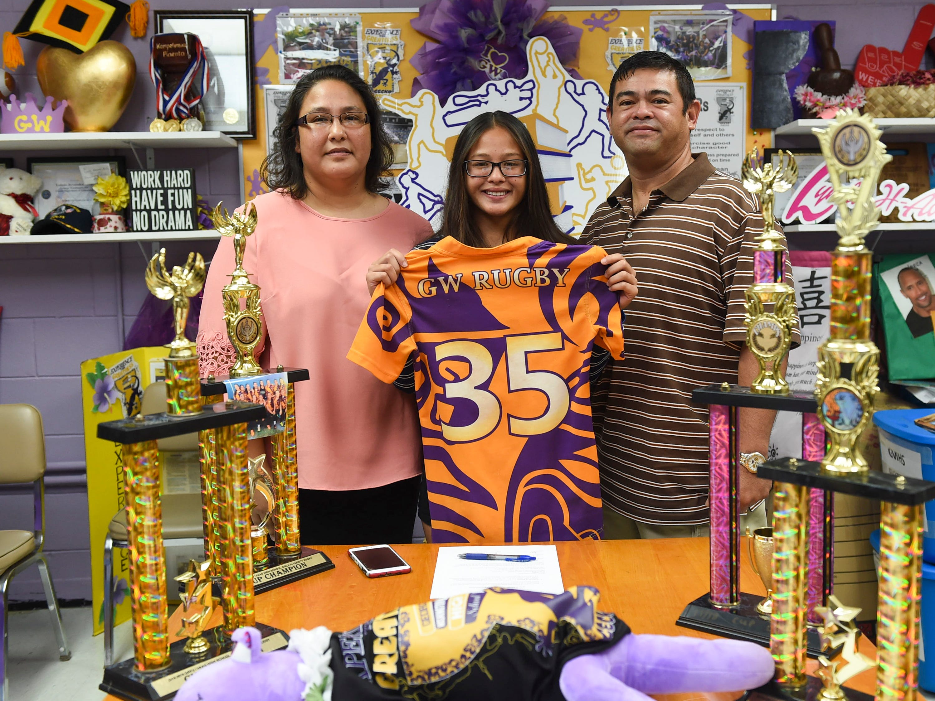 George Washington High School girls' rugby star, Jalana Garcia, 18, beside her parents Ava and Jeffrey Garcia, displays her Geckos team jersey after signing a letter of intent with Mount St. Mary's University, at the GWHS main office, Jan. 11, 2019.