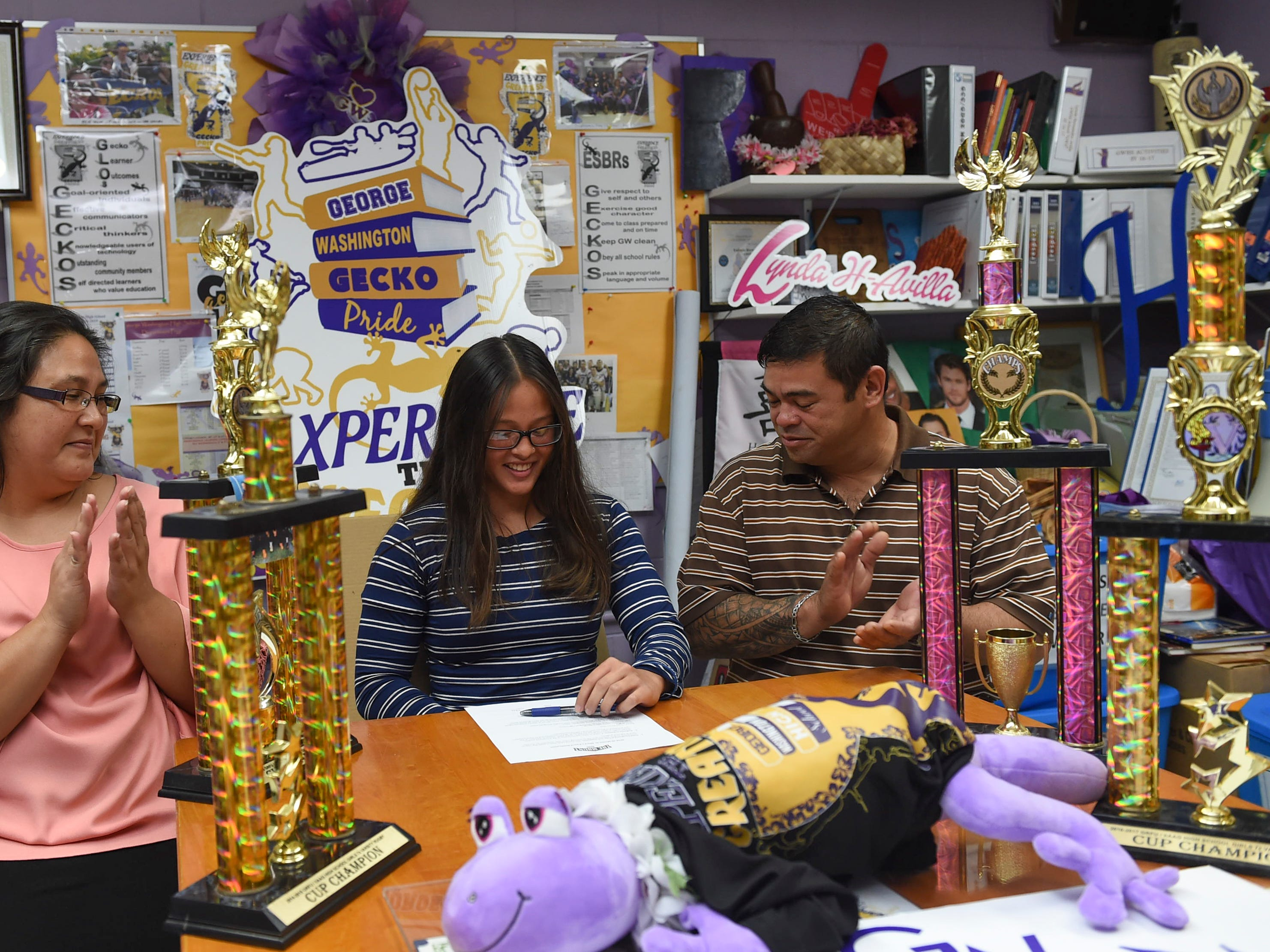 Ava and Jeffrey Garcia applaud after the college signing of their daughter and George Washington High School girls' rugby star athlete, Jalana Garcia, 18, to Mount St. Mary's University, at the GWHS main office, Jan. 11, 2019.