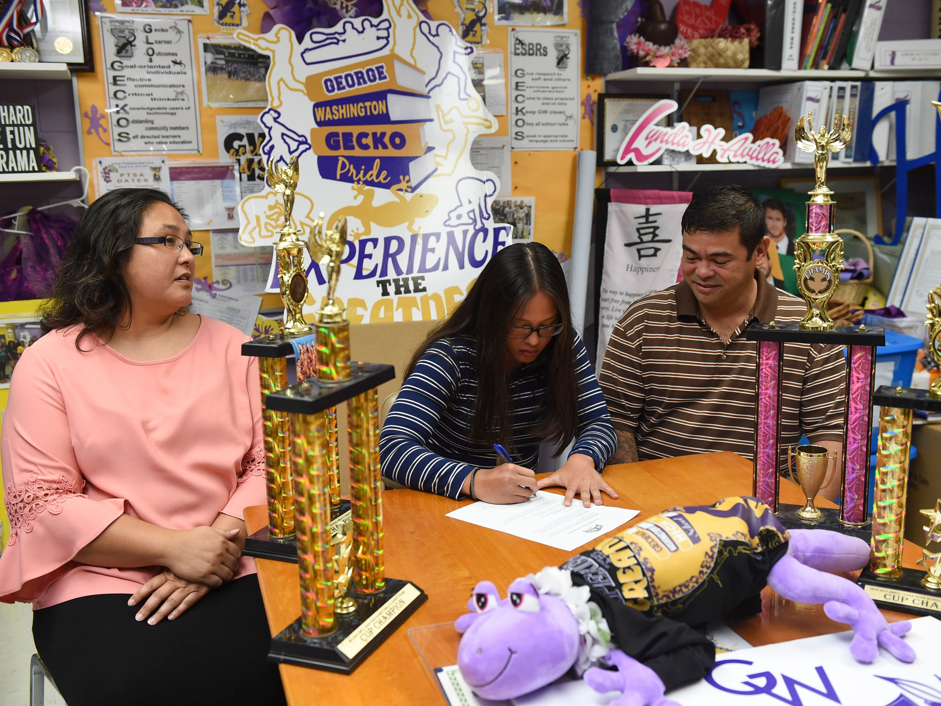 Jalana Garcia, 18, a George Washington girls' rugby star and All-Island athlete, signs a letter of intent to play for with Mount St. Mary's University, beside her parents Ava and Jeffrey Garcia at the GWHS main office, Jan. 11, 2019.