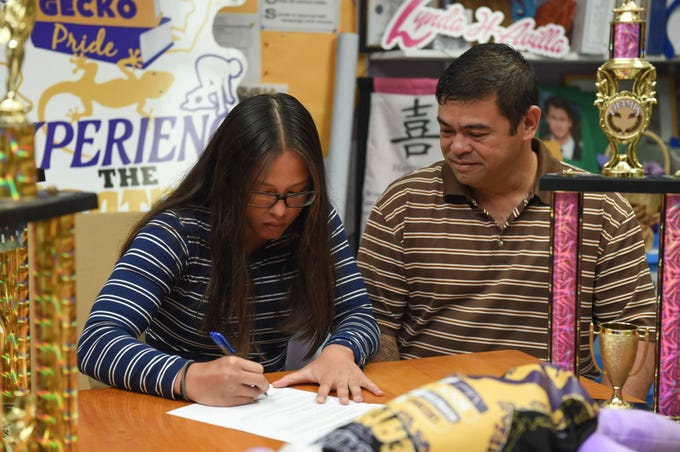 Jalana Garcia, 18, beside her father Jeffrey Garcia, signs a letter of intent to play rugby for Mount St. Mary's University at the George Washington High School main office, Jan. 11, 2019. Garcia, a four-time All-Island athlete and rugby champion, will be getting her GW Geckos No. 35 jersey retired by the school.