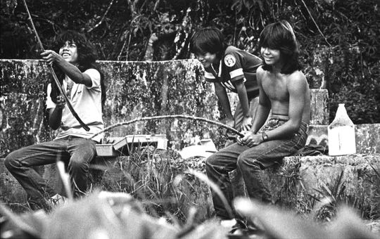 Three friends from Sinajana enjoy fishing for catfish after school in this 1987 photo. From left, they are Frank Santos, 14; John Reyes, 11; and Vince Pinaula, 14.