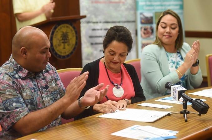Gov. Lou Leon Guerrero, center, signs the Cervical Cancer Awareness Month Proclamation beside Lt. Gov Josh Tenorio and Sen. Amanda Shelton at the Ricardo J. Bordallo Governor's Complex in Adelup, Jan. 11, 2019.