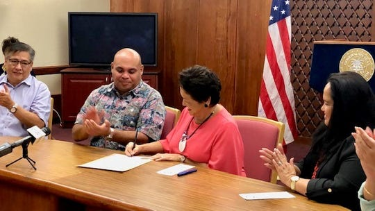 Gov. Lou Leon Guerrero signs on Jan. 11, 2019 her first proclamation as governor, declaring Jan. 13 to 19 as Airport Week 2019, while Lt. Gov. Joshua Tenorio, Speaker Tina Muna Barnes and Guam International Airport Authority board chairman Ricardo Duenas applaud.