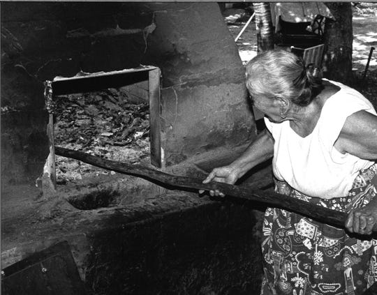 "Tan Rita ""Maria"" Mafnas uses a hotno, or outdoor oven, to bake CHamoru cookies in this 1988 photograph."
