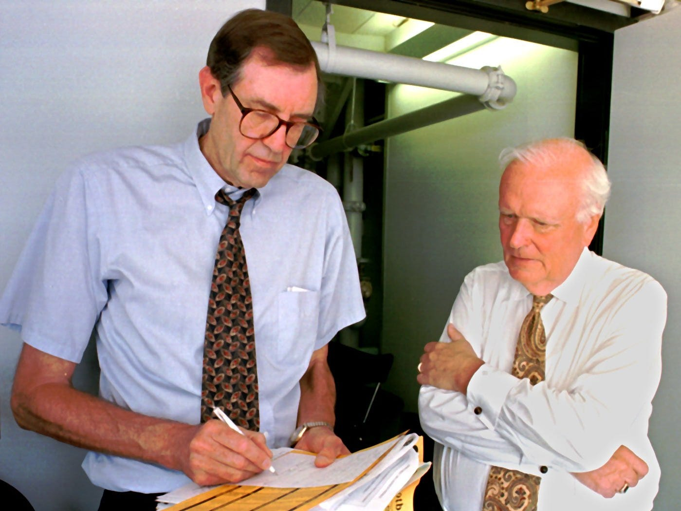 From 1997: Iowa football commentators Ron Gonder, left, and Bob Brooks, right, go over notes in broadcast booth before a game against Northern Iowa.