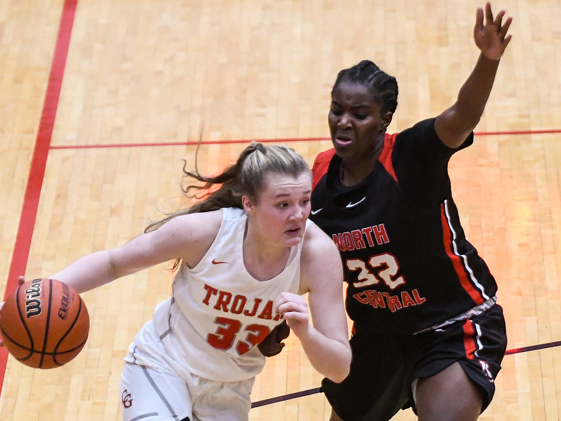 Center Grove Trojans guard Mary Wilson (33) drives the ball around North Central Panthers forward Nakaih Hunter (32) in the second half of the game at Center Grove High School in Greenwood, Ind., Thursday, Jan. 10, 2019. Center Grove defeated North Central, 51-44.