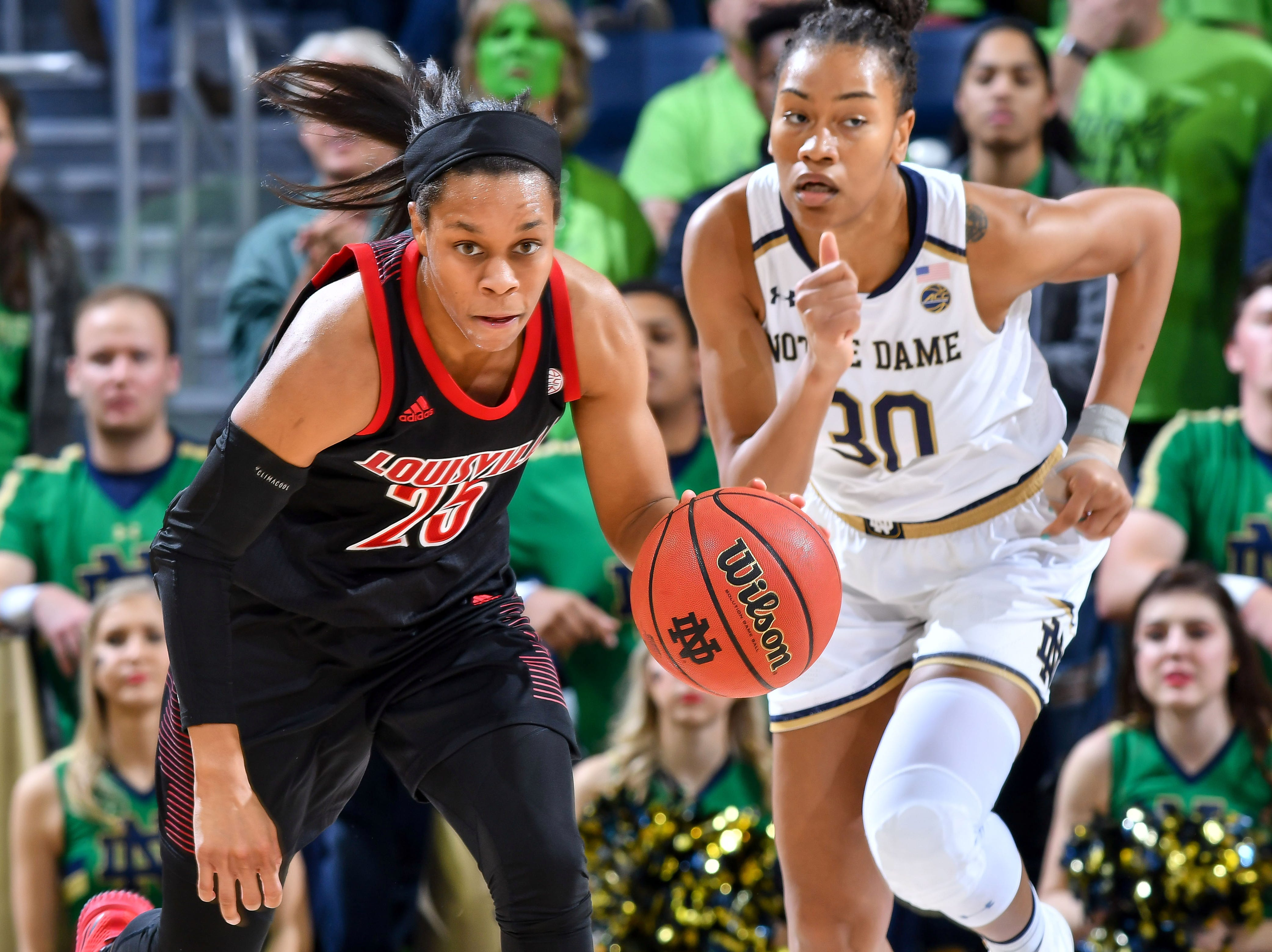 Jan 10, 2019; South Bend, IN, USA; Louisville Cardinals guard Asia Durr (25) dribbles as Notre Dame Fighting Irish center Mikayla Vaughn (30) pursues in the first half at the Purcell Pavilion. Mandatory Credit: Matt Cashore-USA TODAY Sports