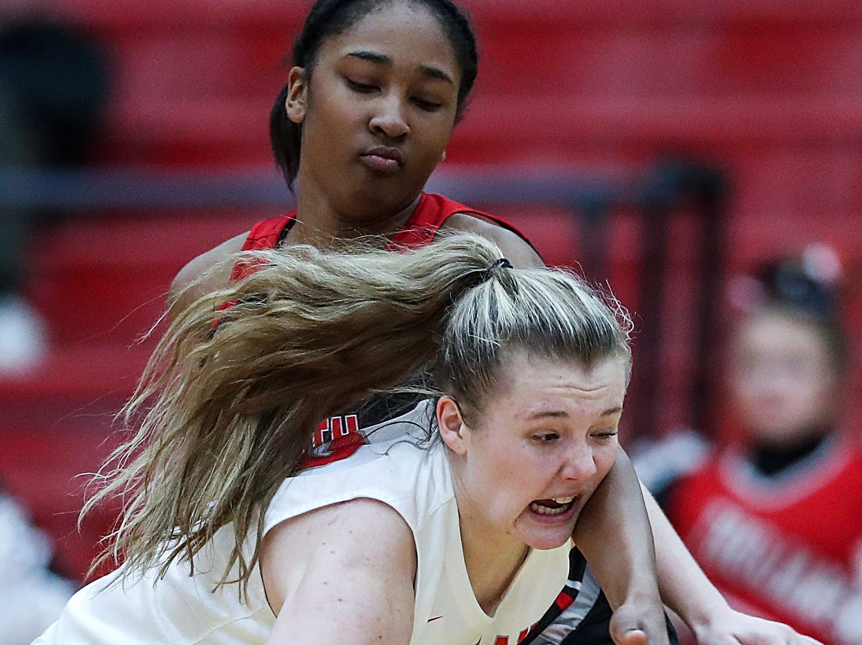 Center Grove Trojans guard Mary Wilson (33) runs into the arm of North Central Panthers forward Ramiah Elliott (20) while working a possession in the second half of the game at Center Grove High School in Greenwood, Ind., Thursday, Jan. 10, 2019. Center Grove defeated North Central, 51-44.