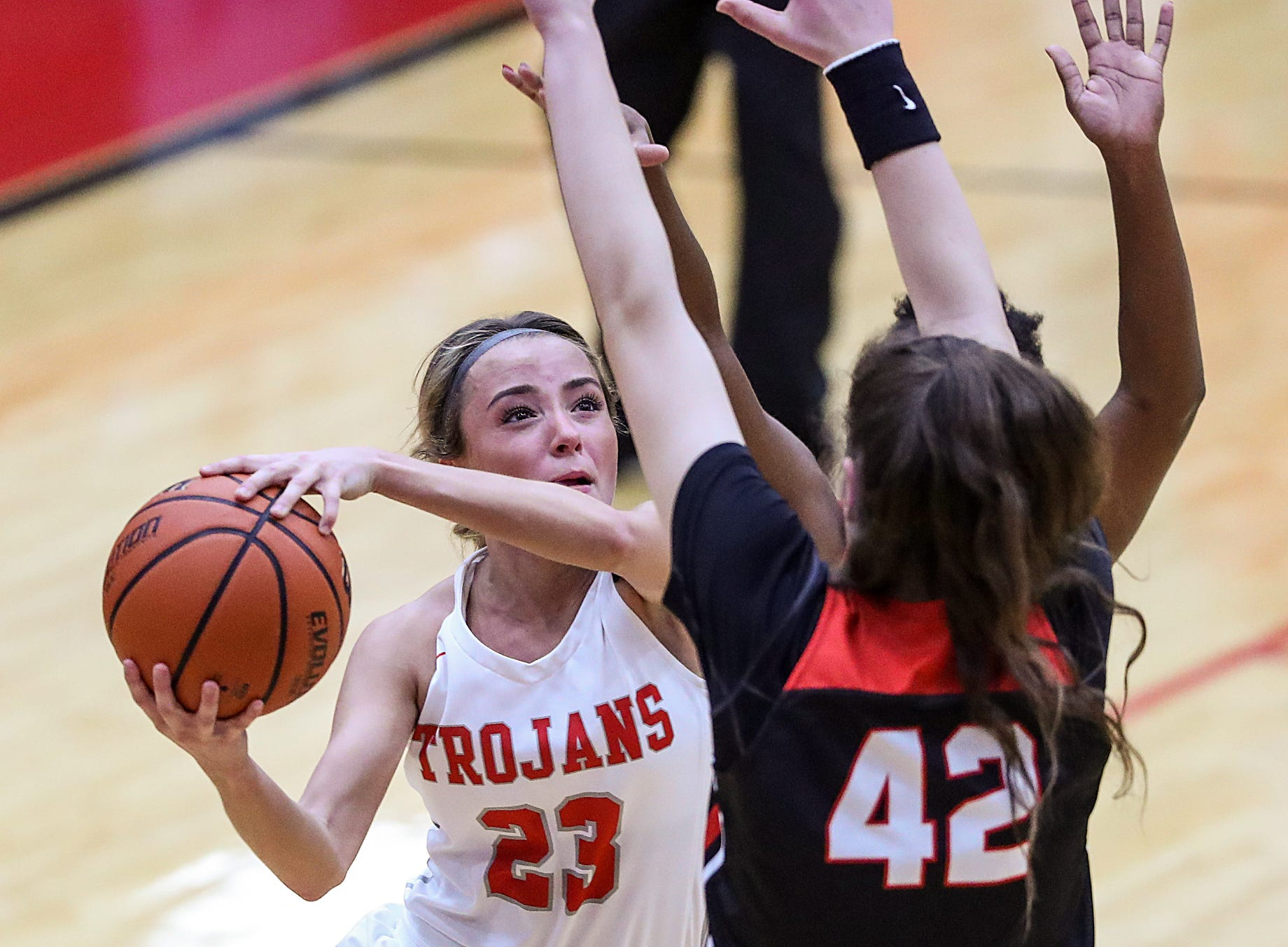 Center Grove Trojans guard Emma Utterback (23) takes a shot between North Central defenders in the first half of the game at Center Grove High School in Greenwood, Ind., Thursday, Jan. 10, 2019. Center Grove defeated North Central, 51-44.
