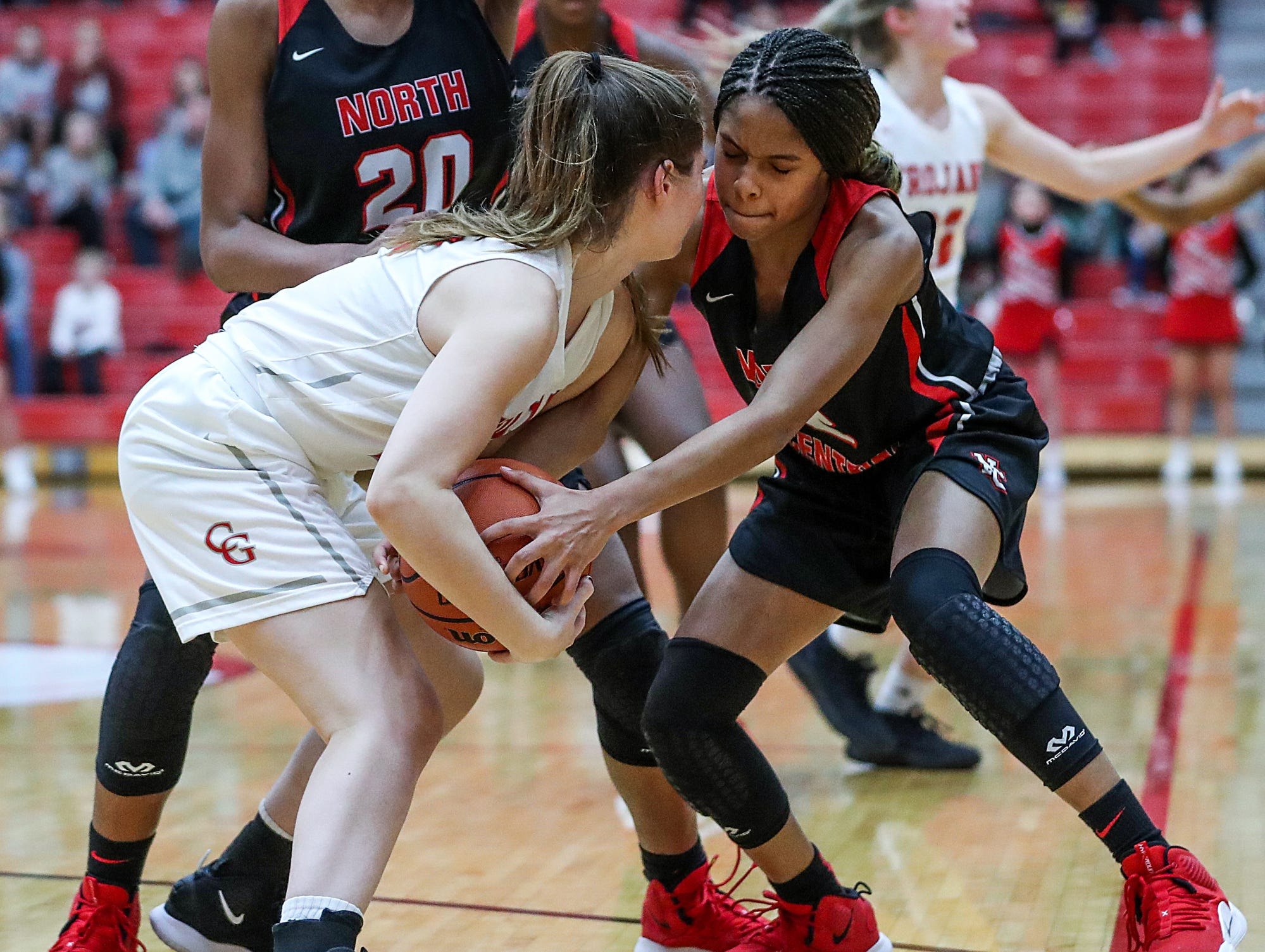 Center Grove Trojans Claire Rake (12) and North Central Panthers guard Tanyuel Welch (2) fight for the ball, in a play that ended with a foul on Welch, late in the fourth quarter of the game at Center Grove High School in Greenwood, Ind., Thursday, Jan. 10, 2019. Center Grove defeated North Central, 51-44.