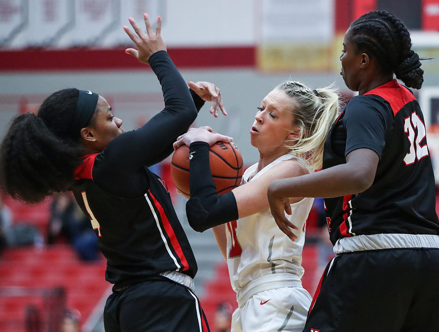 North Central Panthers Savaya Brockington (4) and Nakaih Hunter (32) surround Center Grove Trojans forward Kylie Storm (15) in the first half of the game at Center Grove High School in Greenwood, Ind., Thursday, Jan. 10, 2019. Center Grove defeated North Central, 51-44.